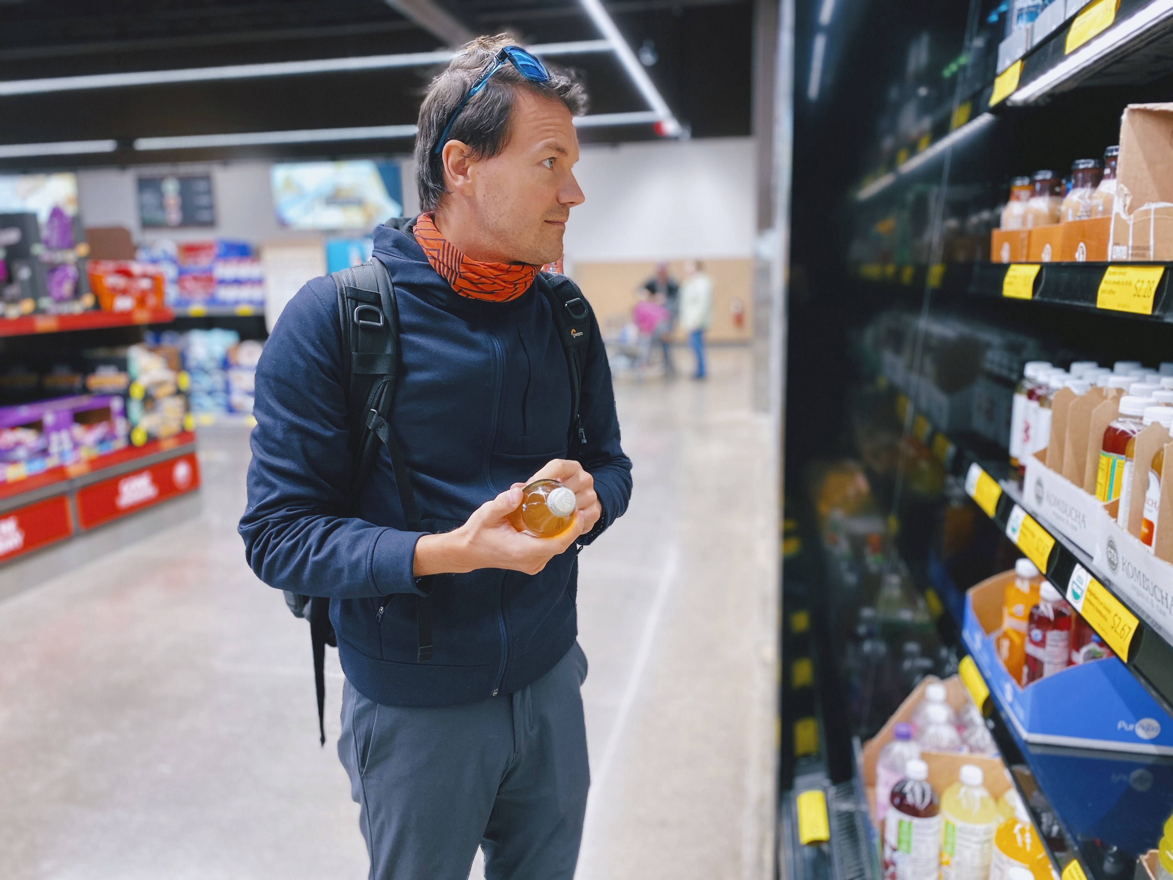 Man looks at juices in the grocery store.