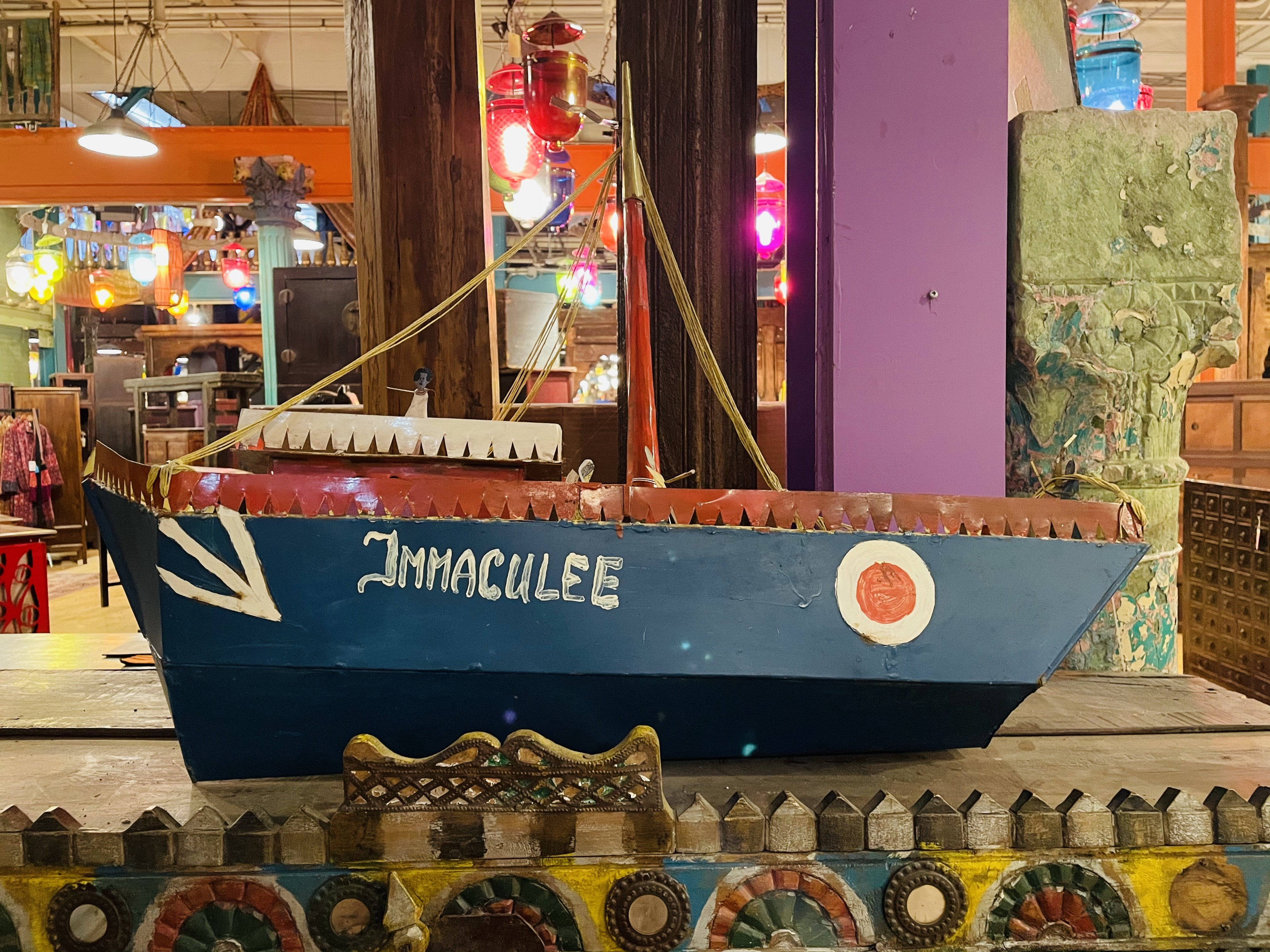 A folk-art boat on a shelf in a colorful room. The boat's name is painted on the hull: Immaculee