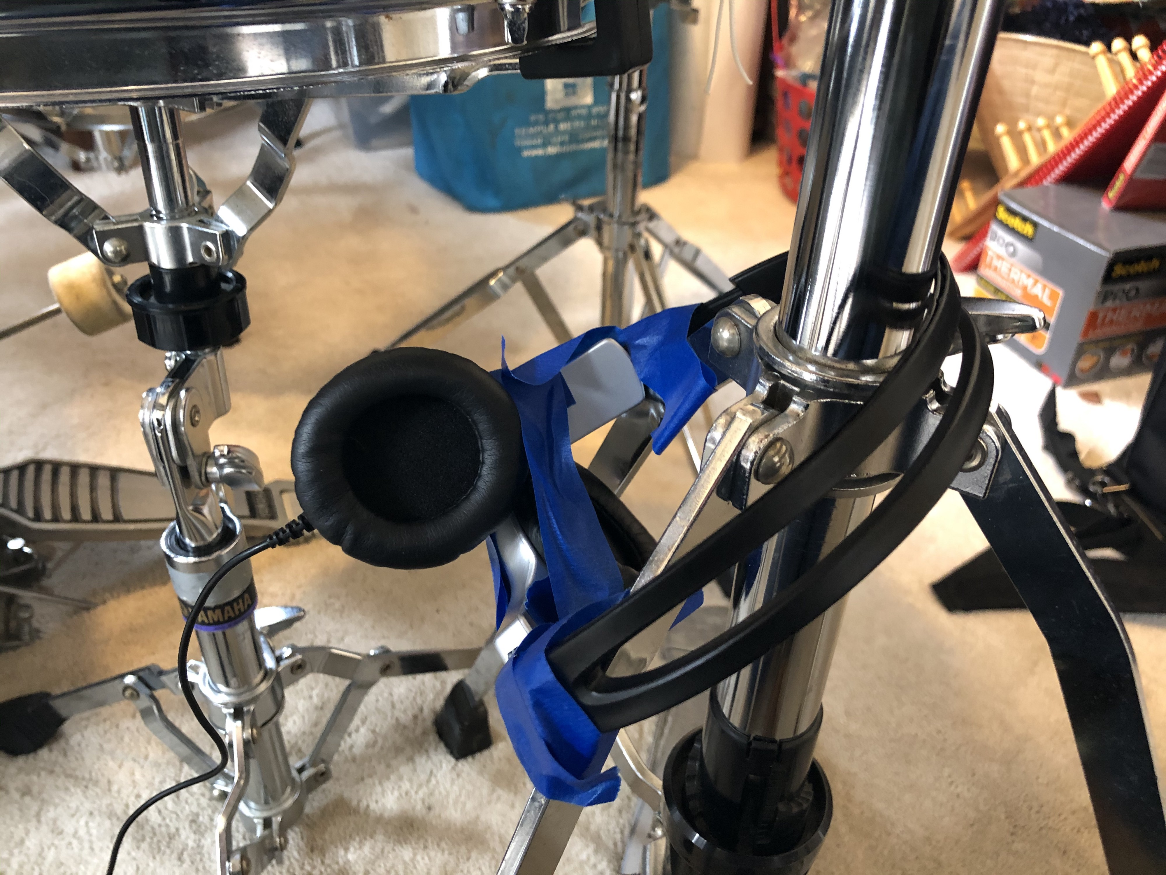 Headphones taped to a hi-hat stand.