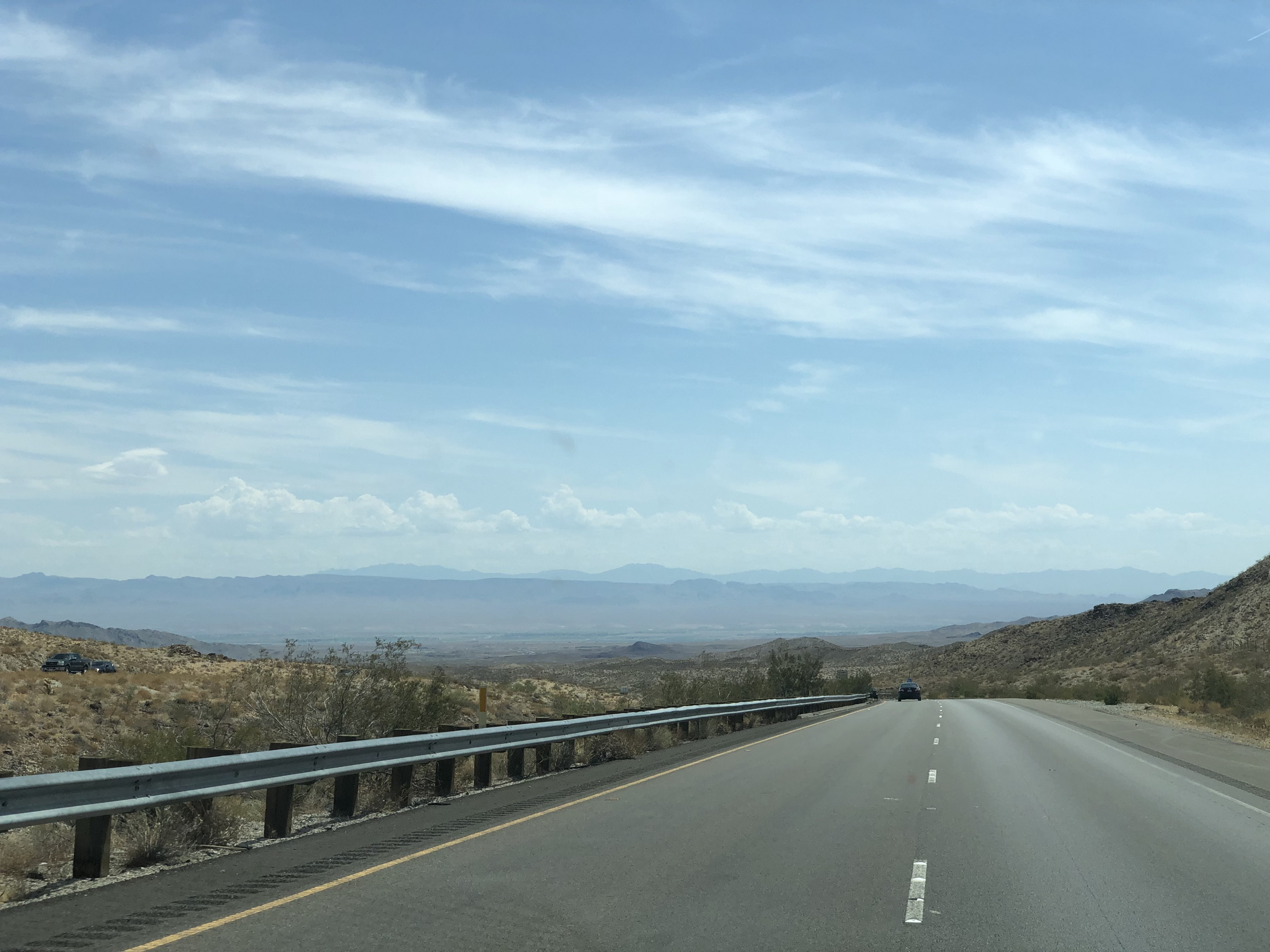 Picture taken from a car on a highway on a hillside, showing an expansive view of a desert basin and far-off mountains.
