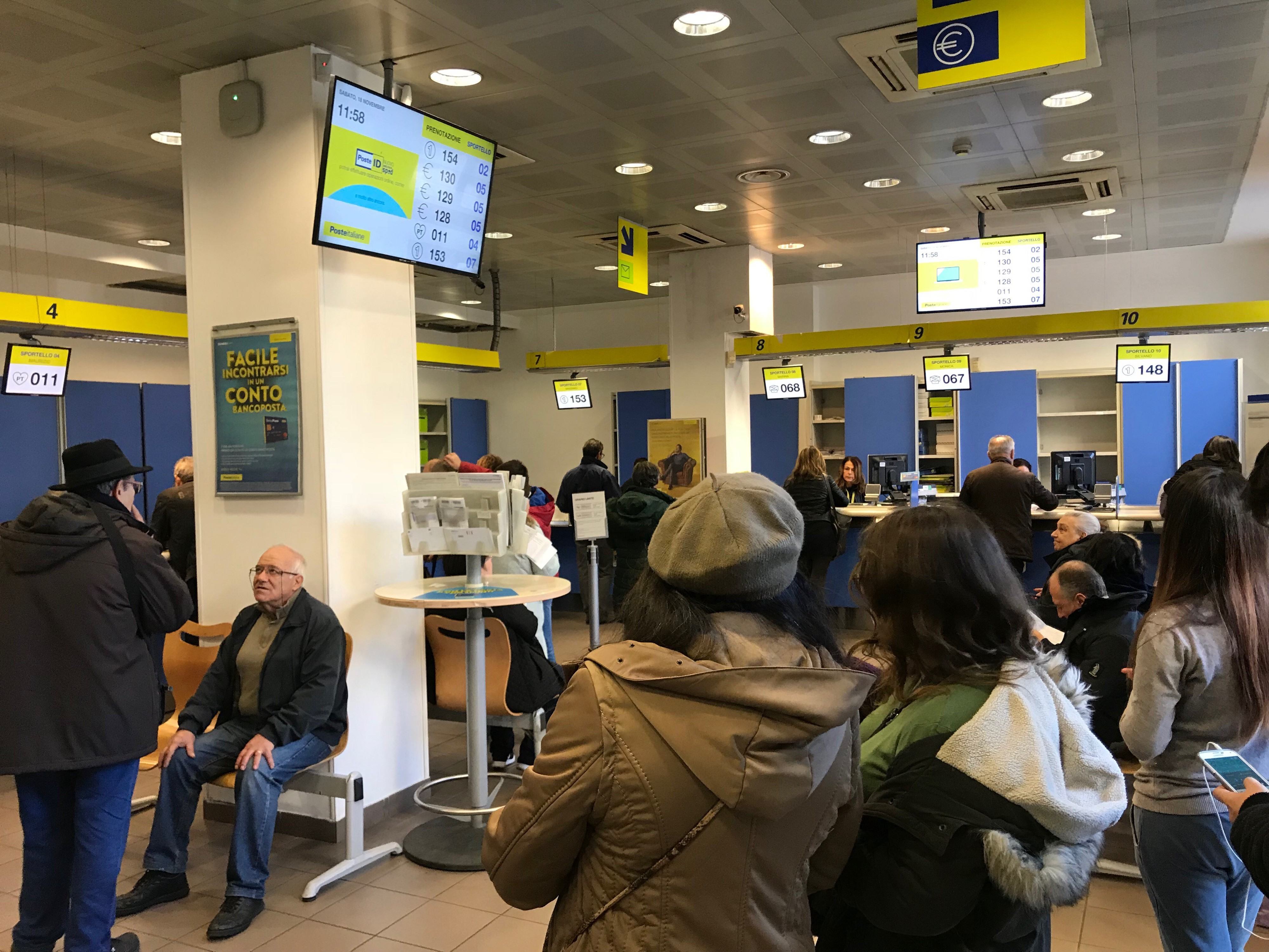 Scene of an Italian postoffice, complete with old folks and the waiting time contraption overhead