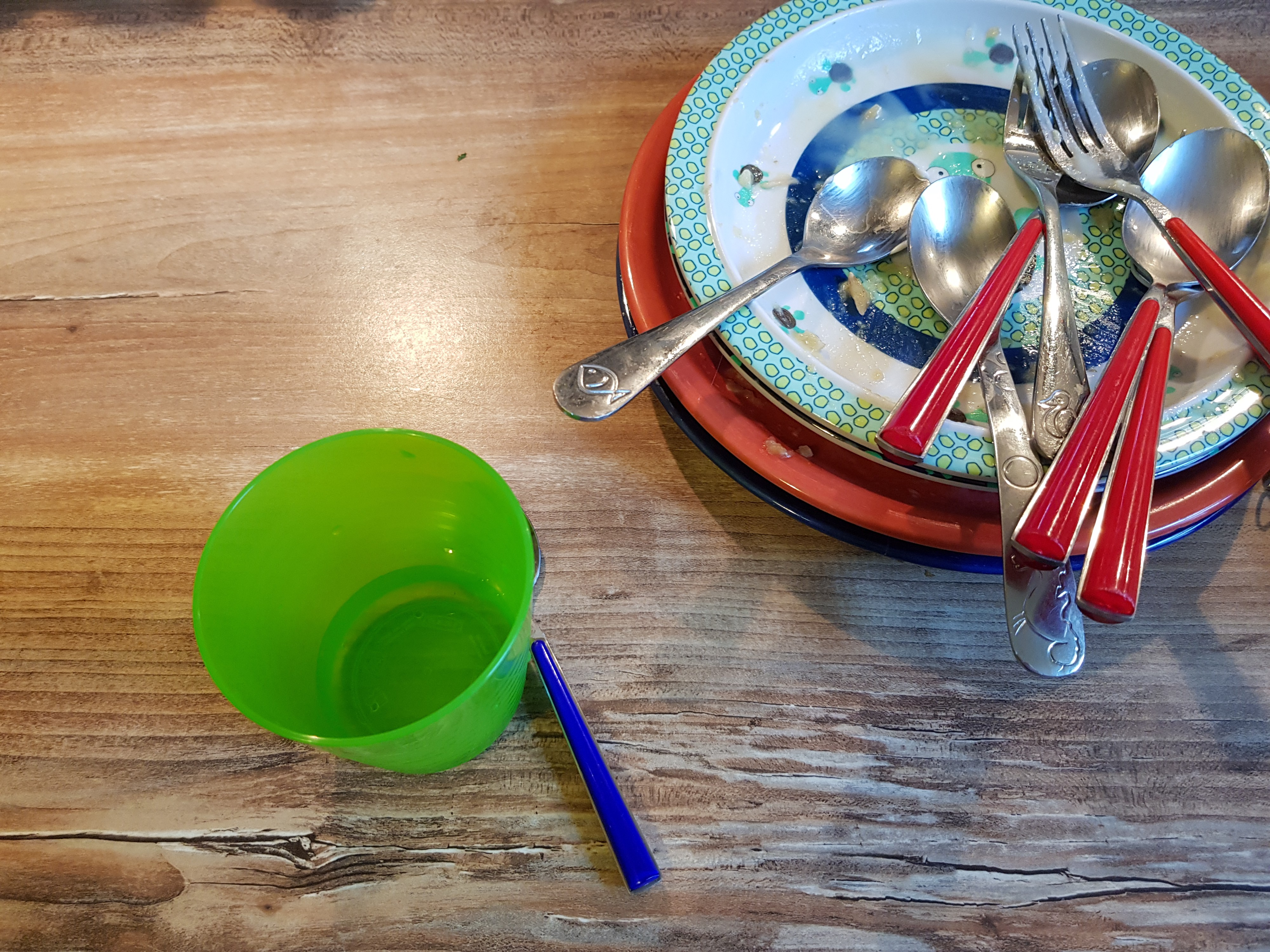 A plastic cup and a pile of plates and cutlery on a wooden countertop.