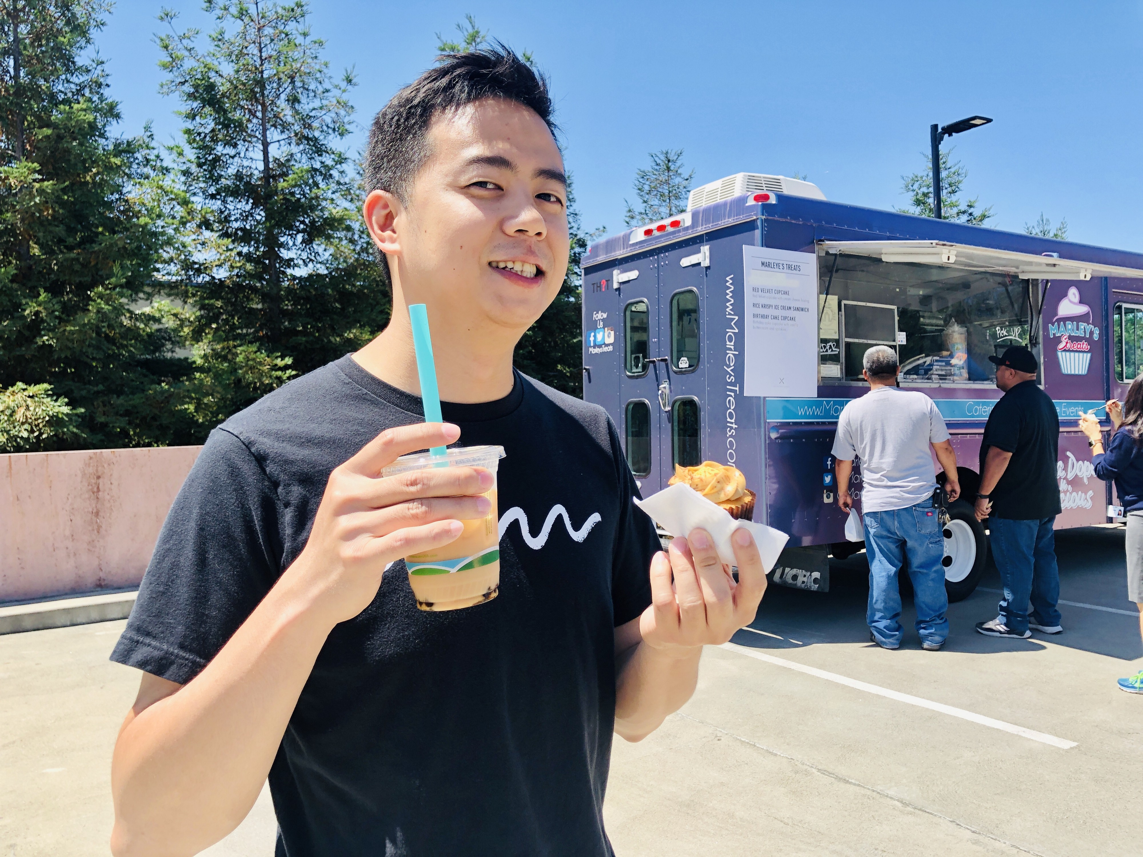 Chit Meng smiling while holding boba and a cupcake