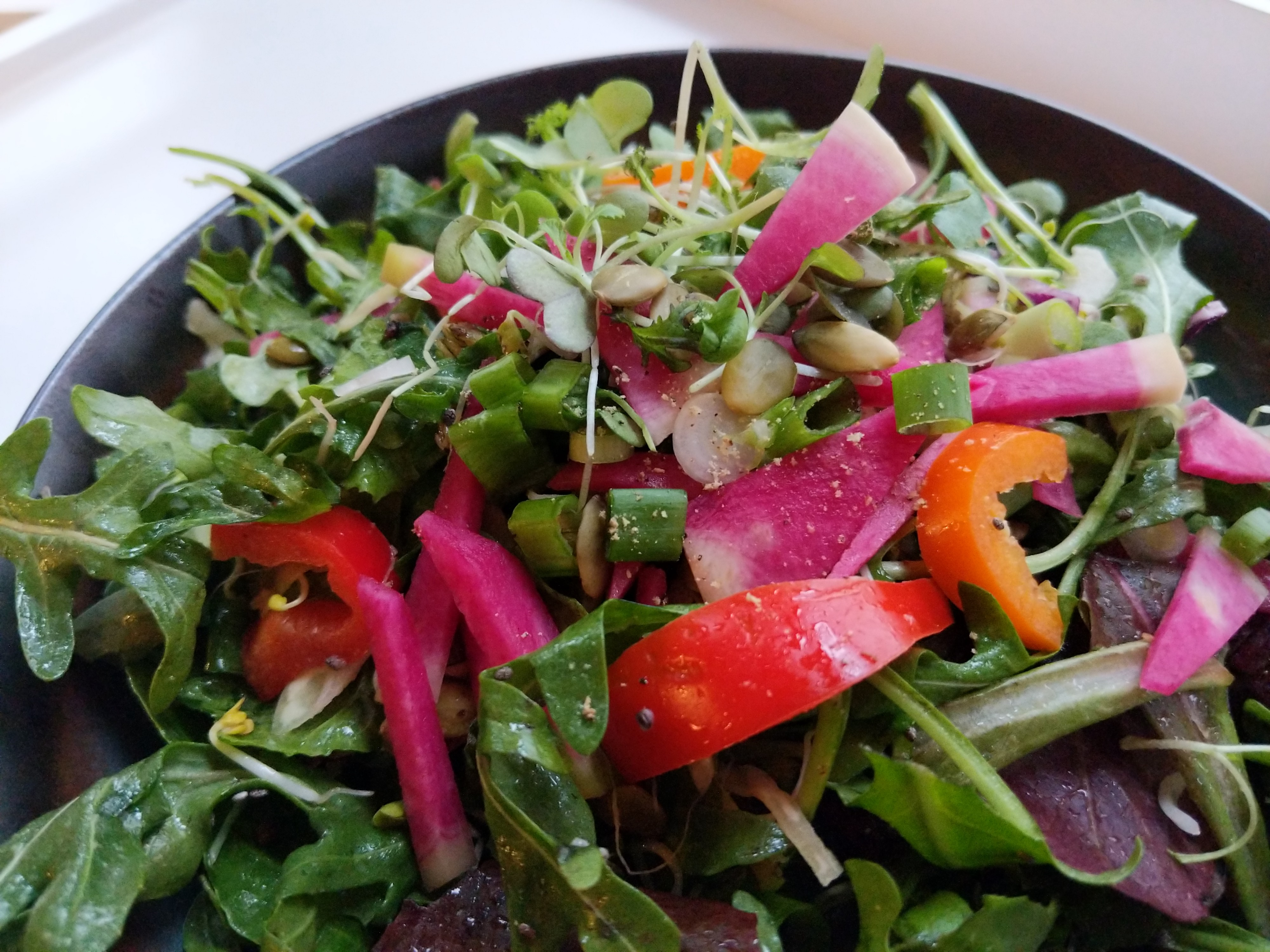 Bowl of fresh salad including arugula, sweet bell peppers, watermelon radish, pumpkin seeds, green onions, and microgreens.
