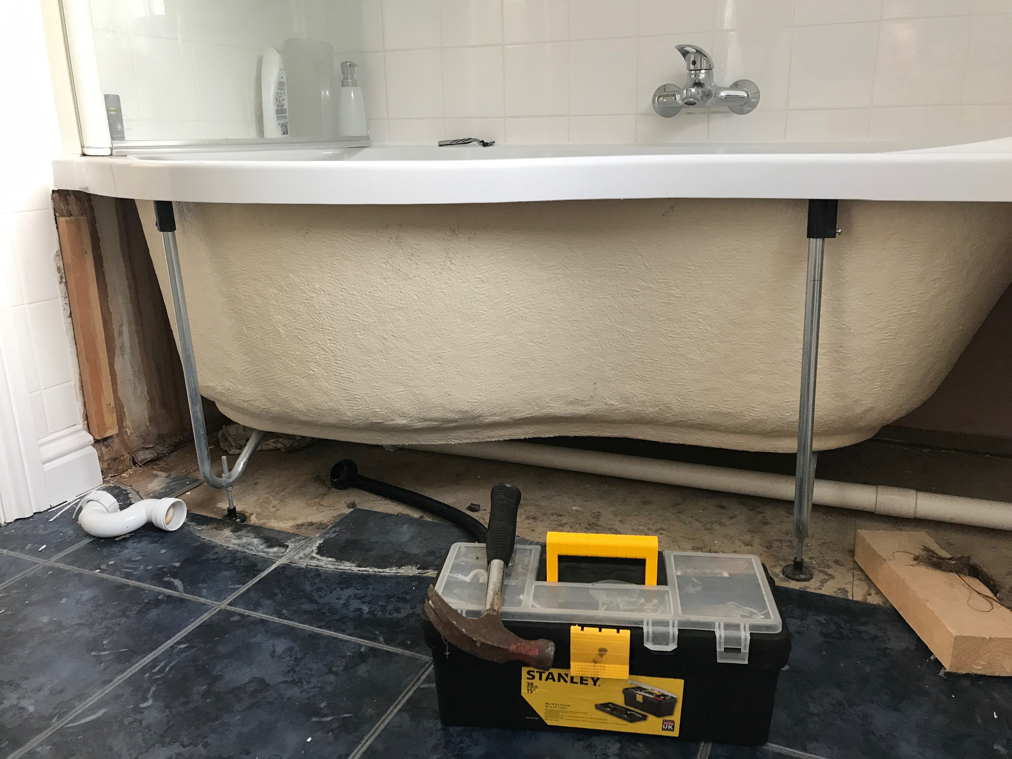 A bath with the side panel off and the pipes exposed