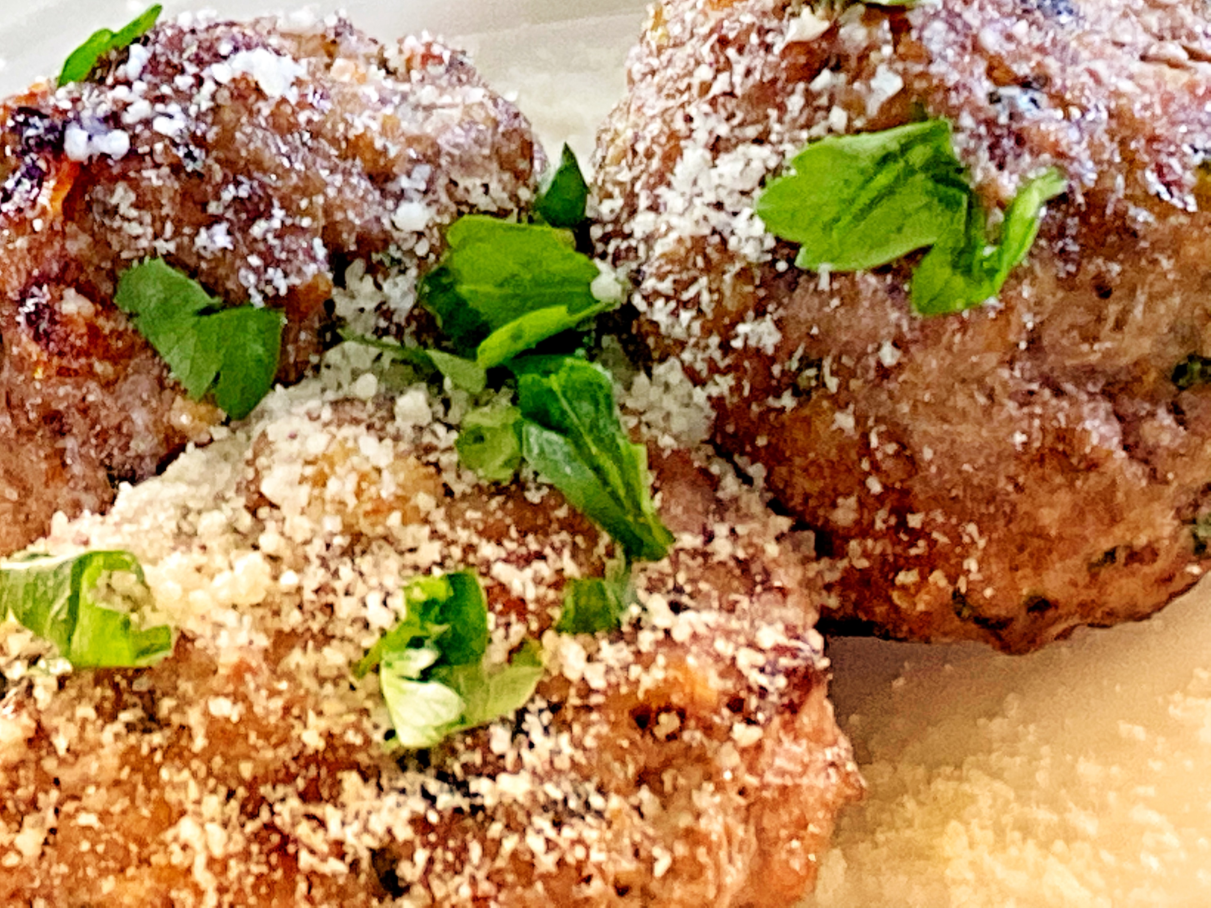 3 meatballs, browned on the outside and sprinkled with parmesan cheese and parsley.