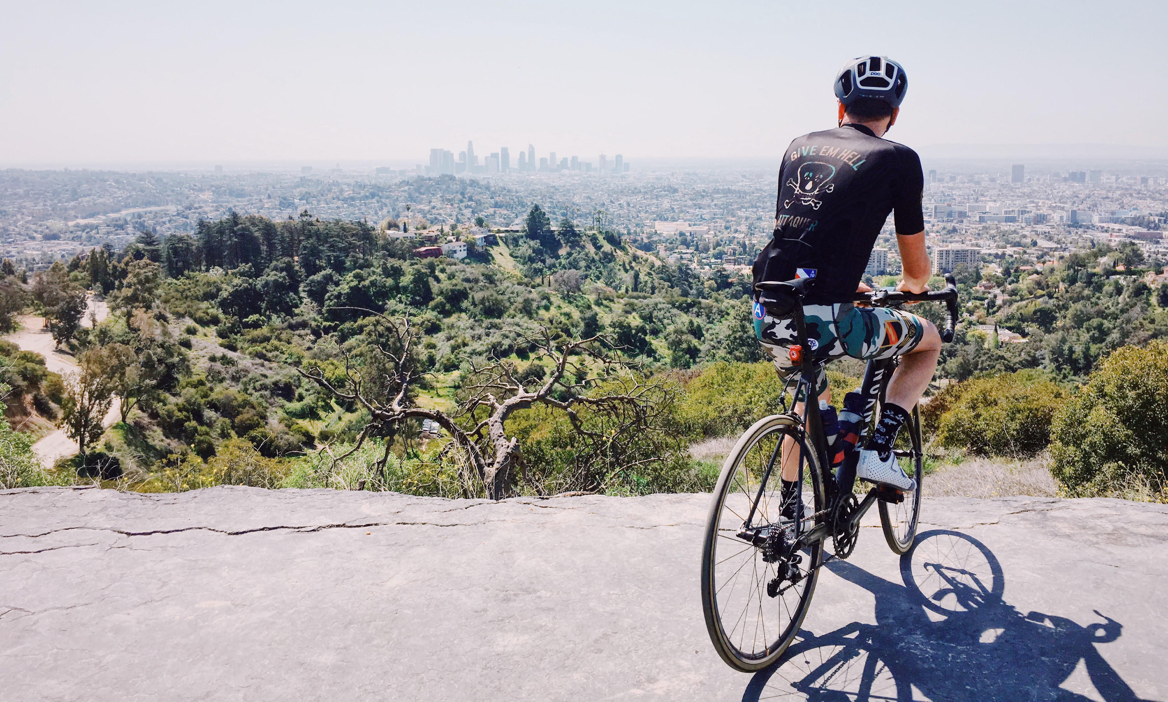 A cyclist poses at the Griffith Park Helipad, which overlooks the skyscrapers of downtown Los Angeles