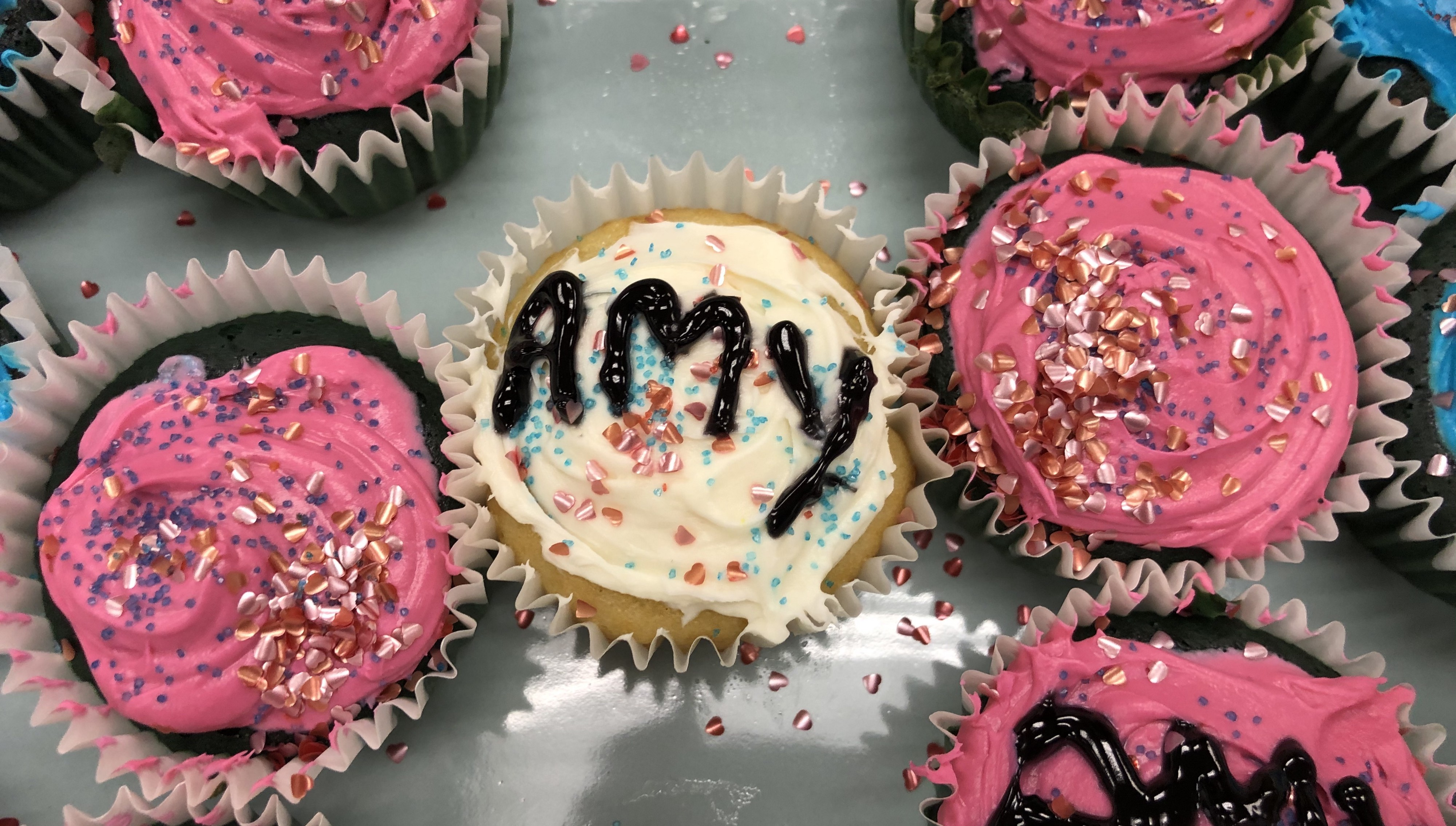 A photograph of a frosted cupcake with the name Amy on it.