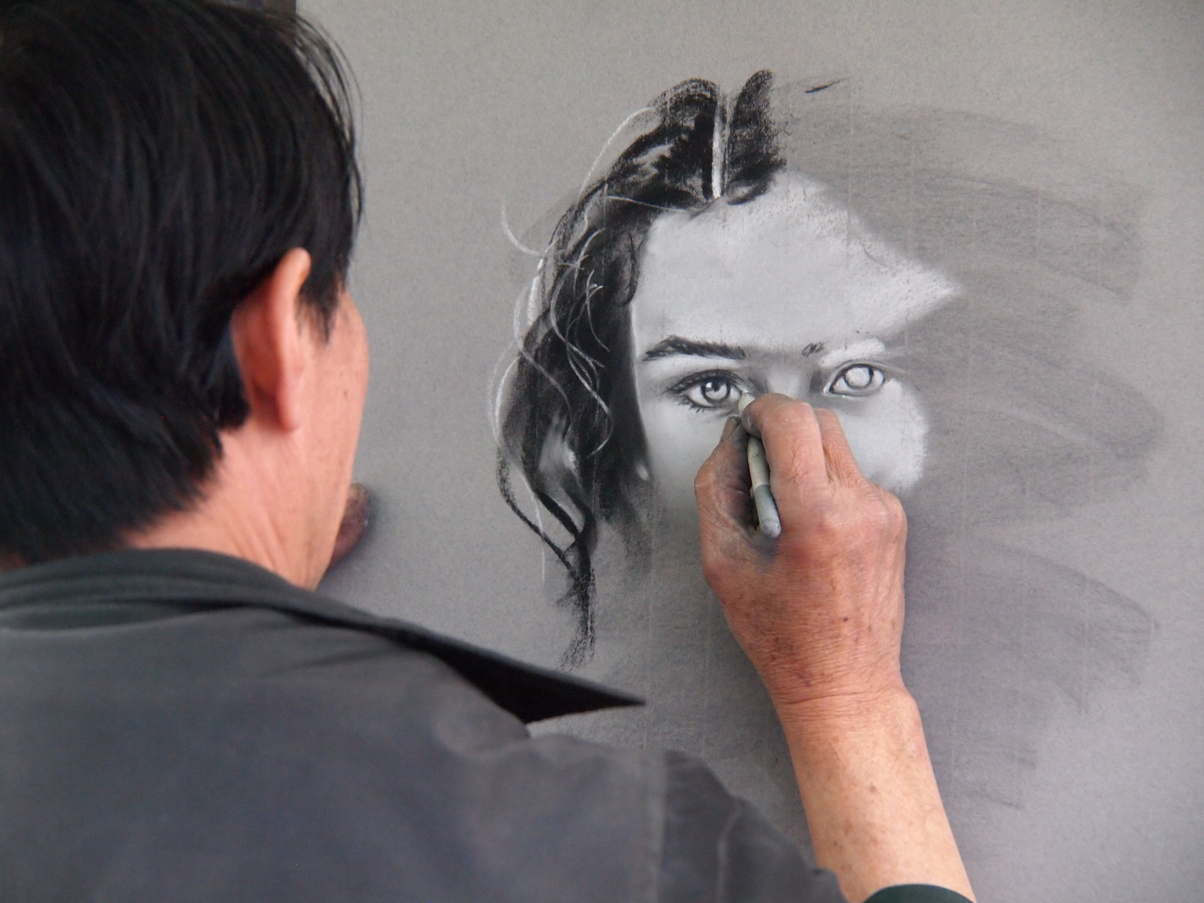 A man painting a woman's face on a grey canvas