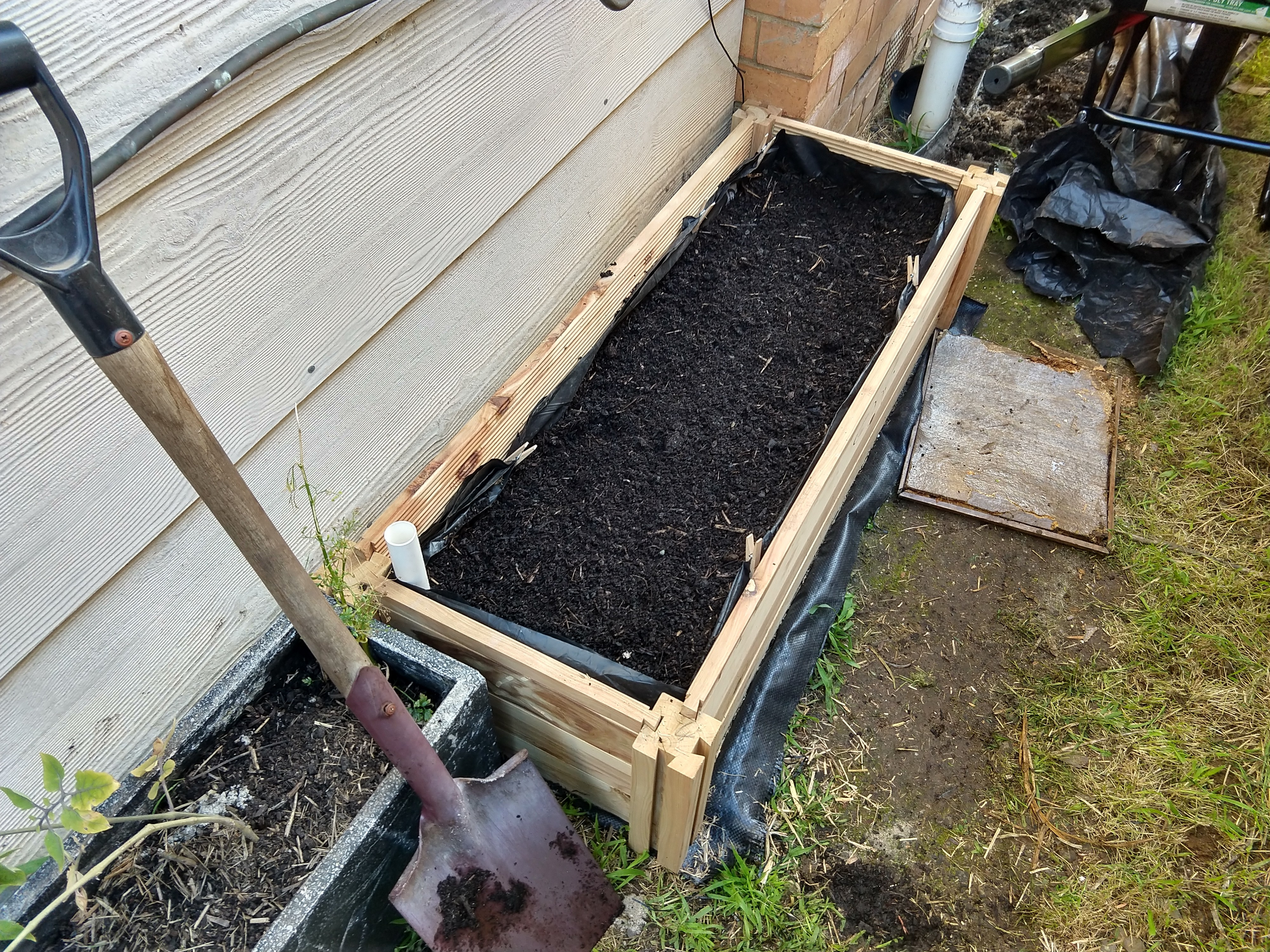 A garden bed against the wall of a house, filled with soil.