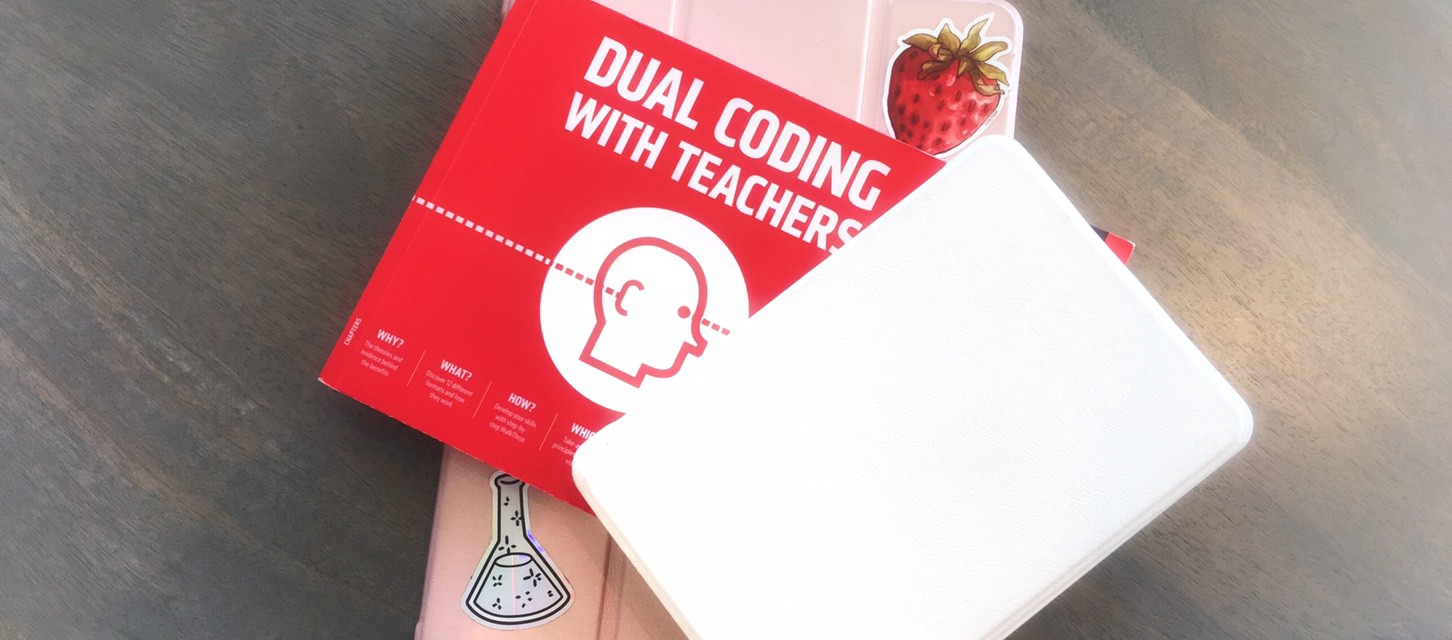 Pink iPad with strawberry and conical flash sticker, 'dual coding with teachers' book, and white kindle in pile on wood.