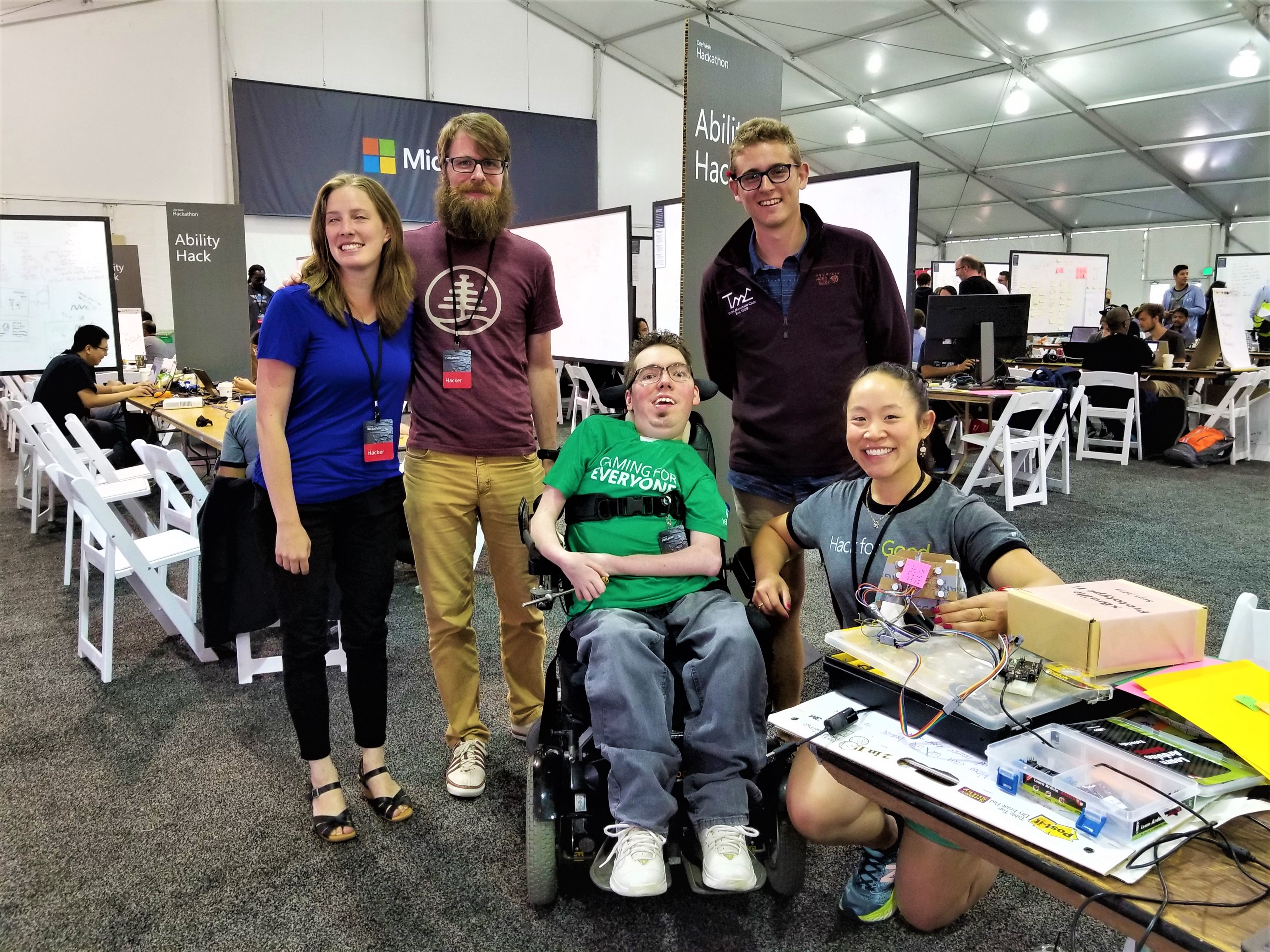 Inside the Hackathon tent, a team of five researchers, designers, and engineers pose with a prototype, all smiles.