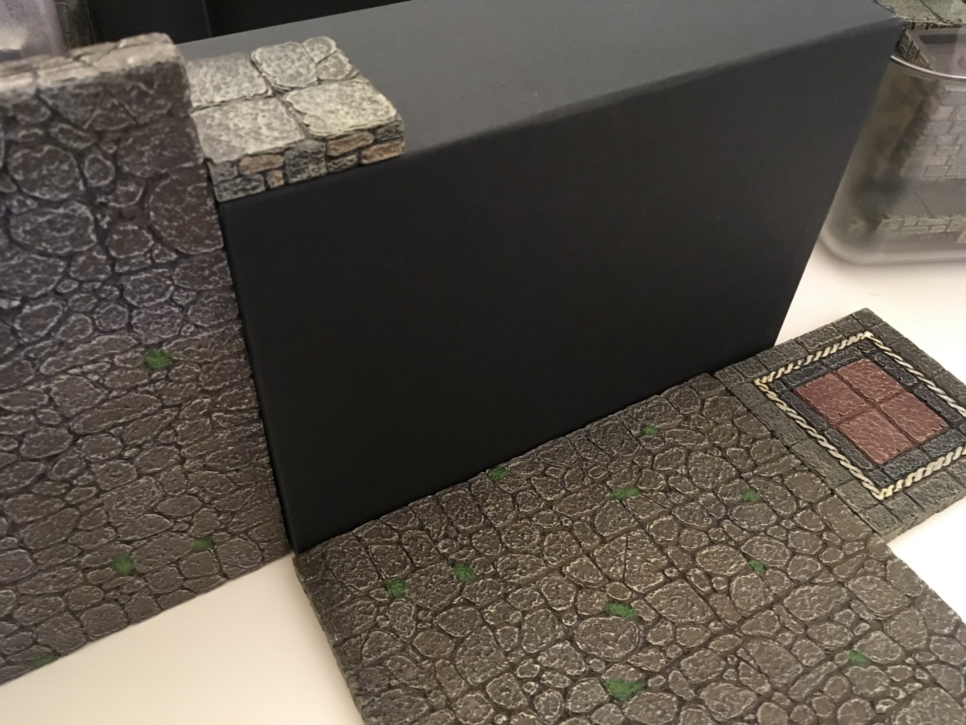 Dwarven Forge floor pieces are used next to the box to indicate its size for game purposes