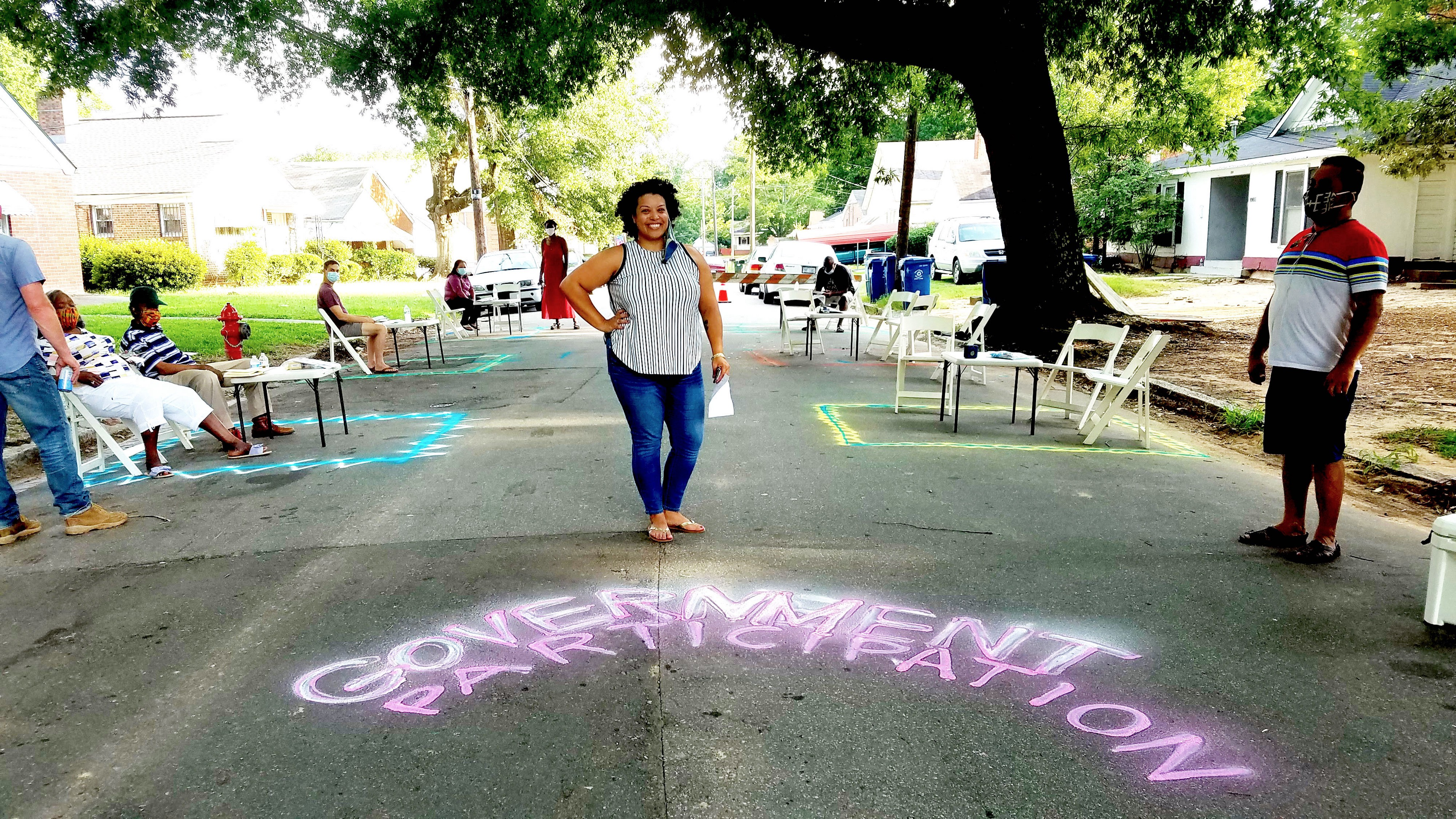 """Aidil Ortiz stands in the middle of a residential street, smiling. At her feet is written """"Government participation"""" in chalk paint. Along the curb on either side of her are tables with chairs set up, so residents can meet and discuss."""