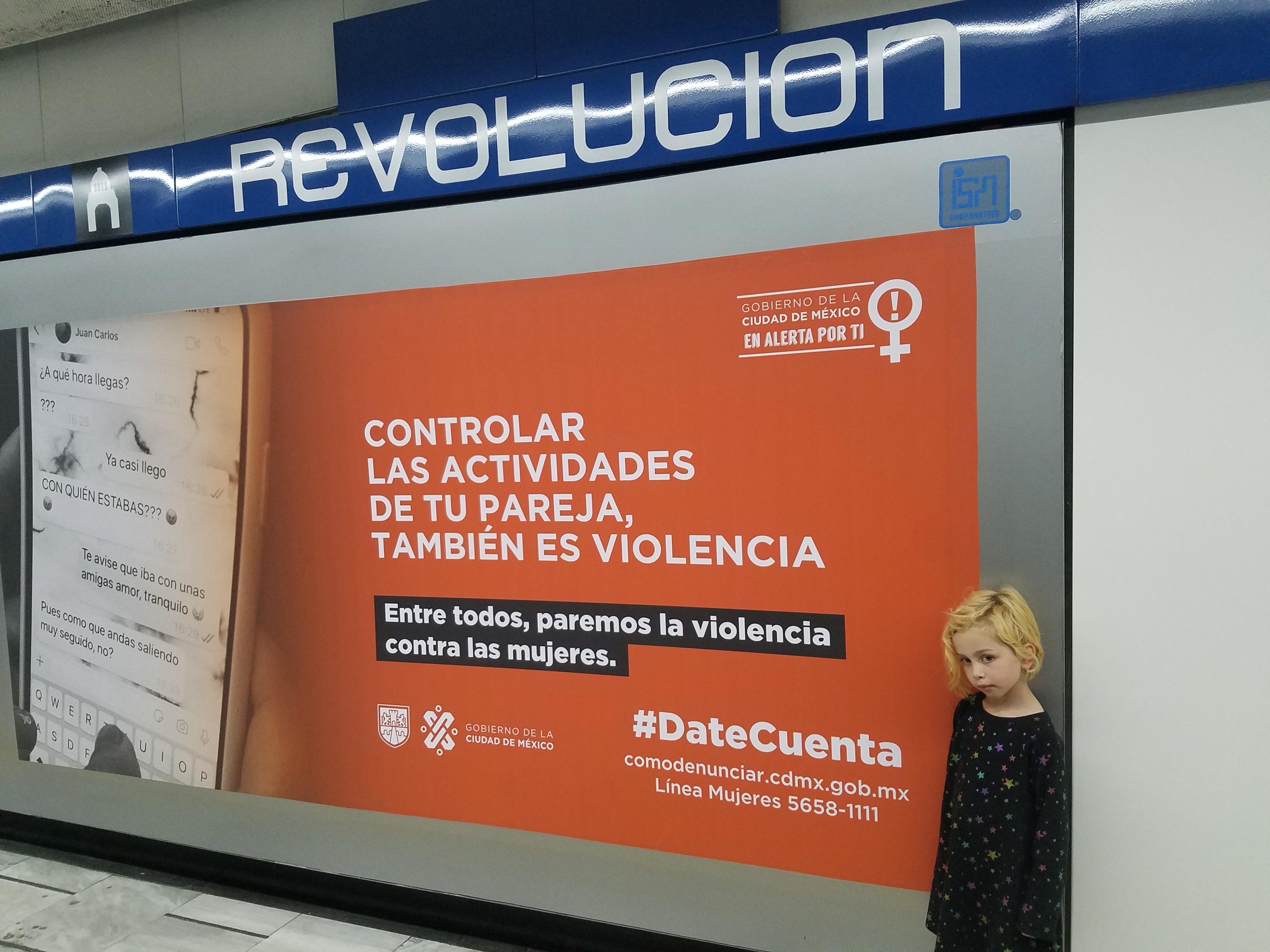 Blonde girl stands in front of a #DateCuenta poster in the CDMX Metro station, under the sign for subway station REVOLUCIÓN