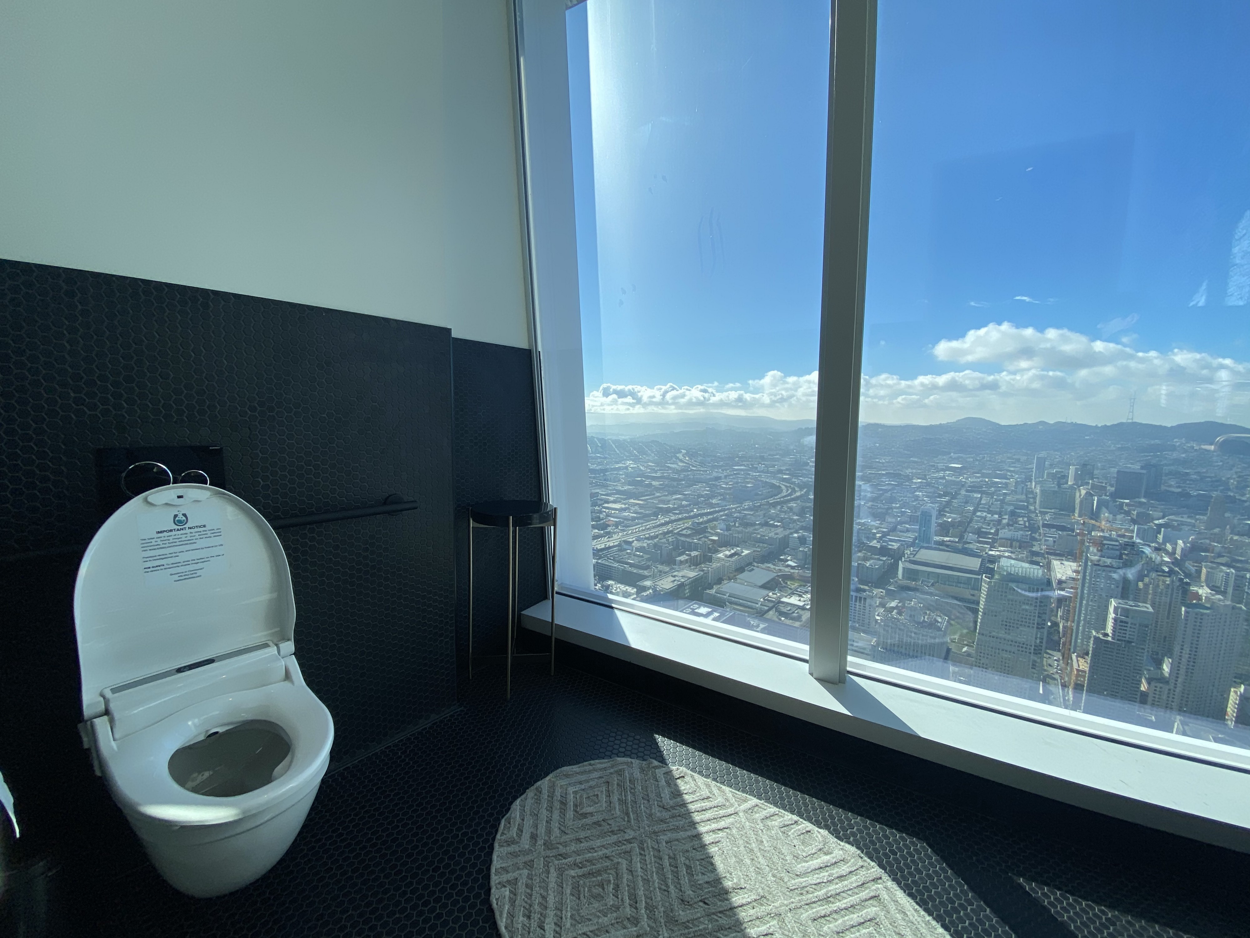 A photo of a smart toilet in a bathroom within a high-rise building overlooking the city.