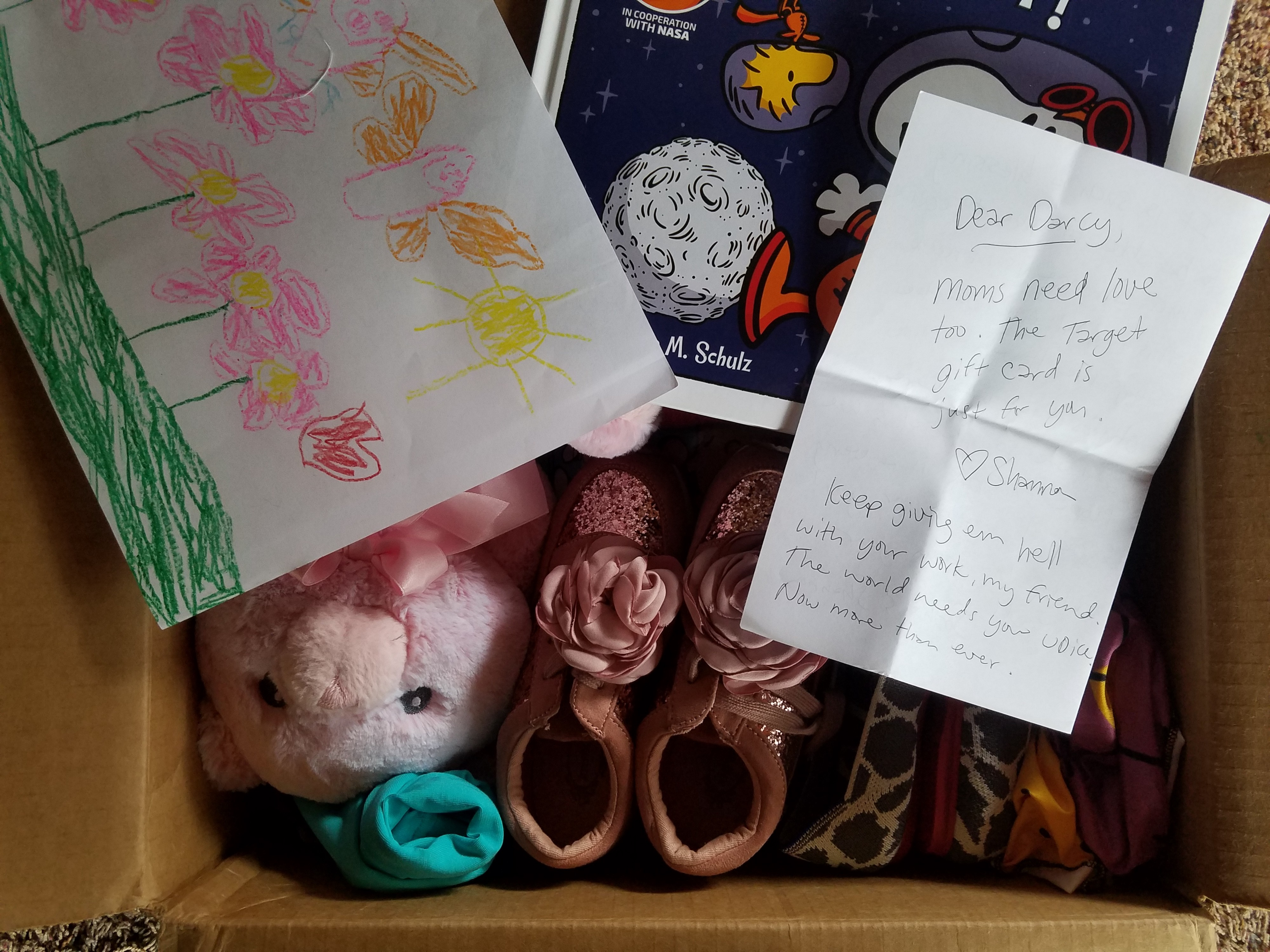 Cardboard box full of goodies: shoes, stuffed bunny, kid art, children's book about space