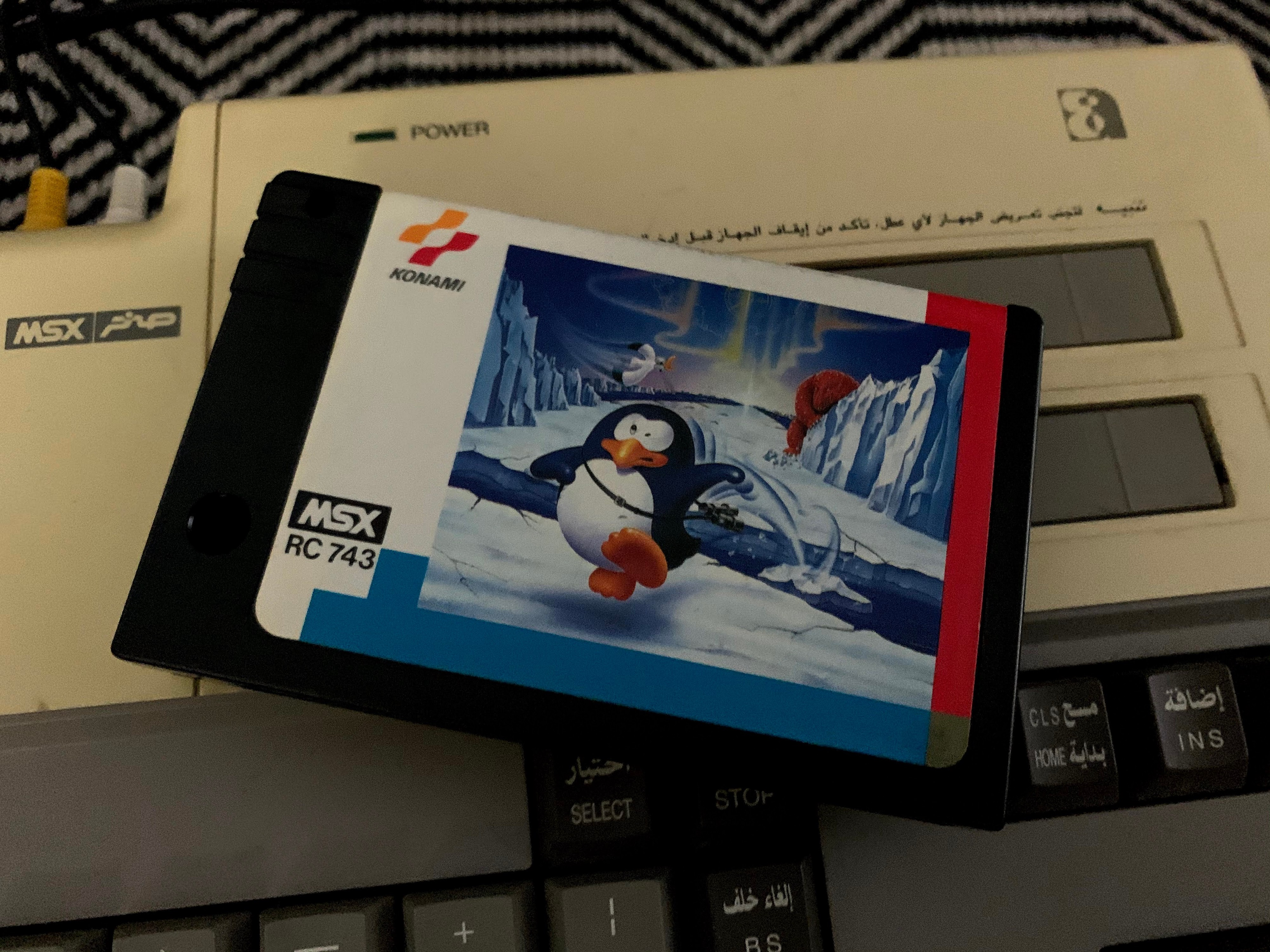 Penguin Adventure game cartridge on top of the Sakhr video game console.