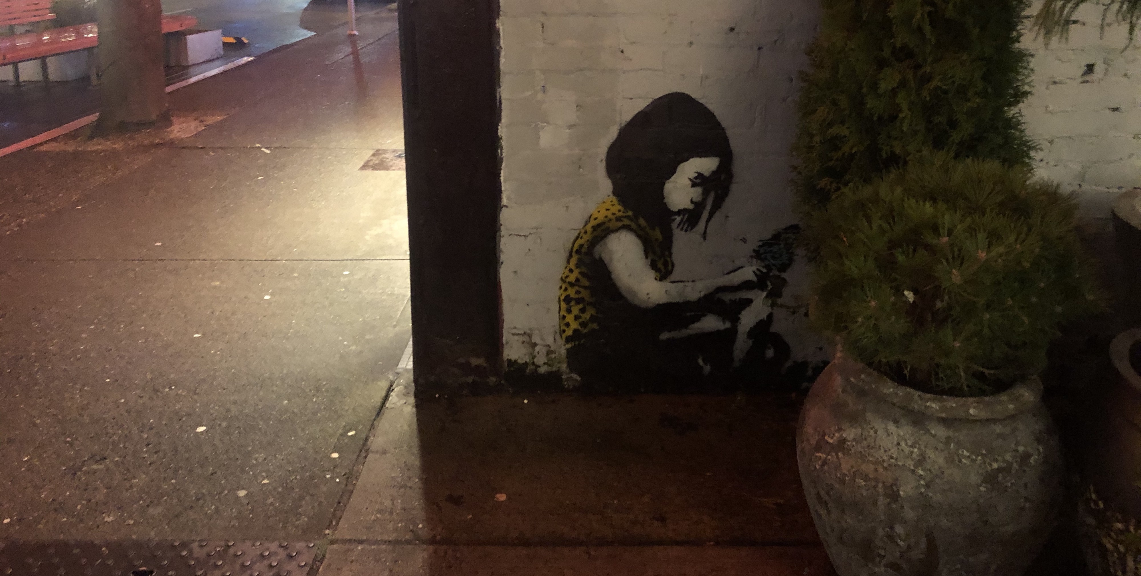 Street art of a girl, sitting in a corner, maybe with a book, looking a bit.