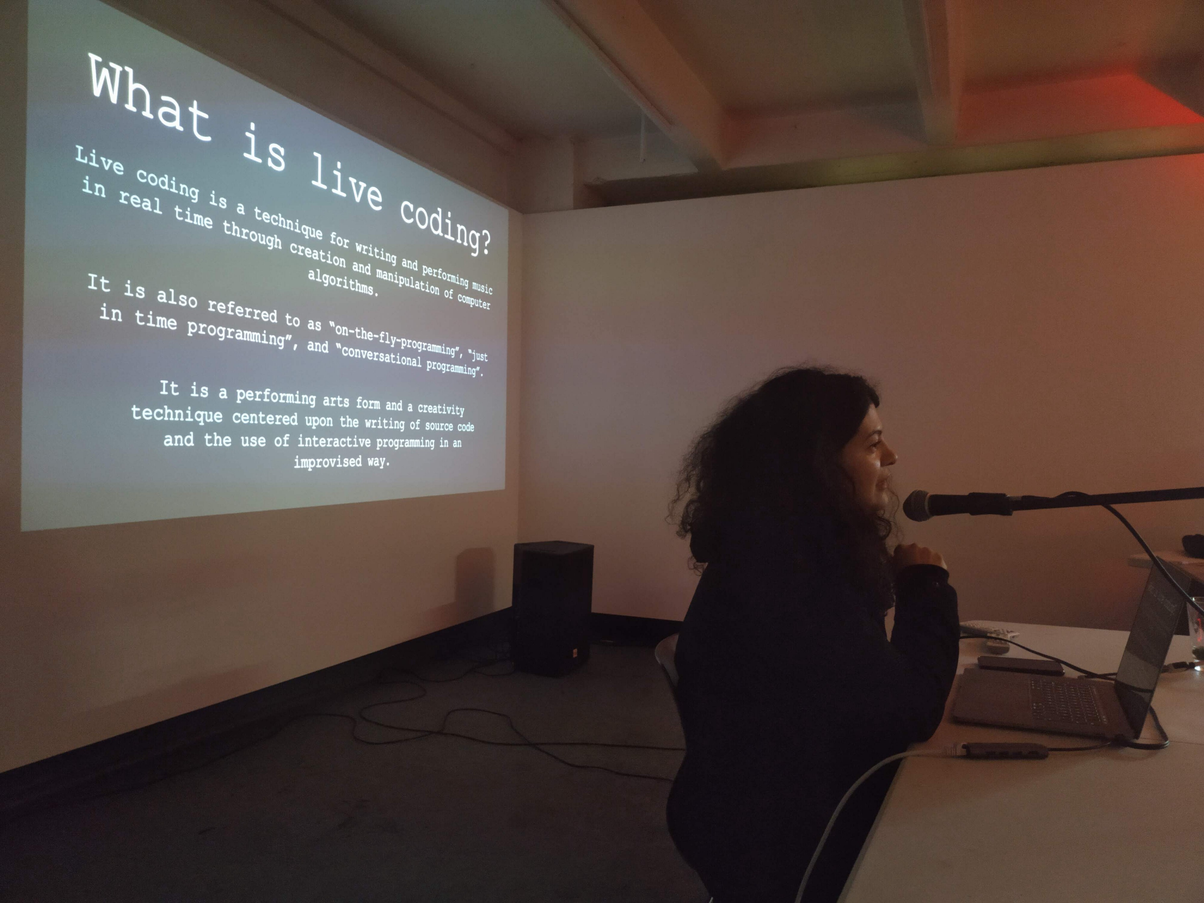 Alexandra talks to the crowd about live coding