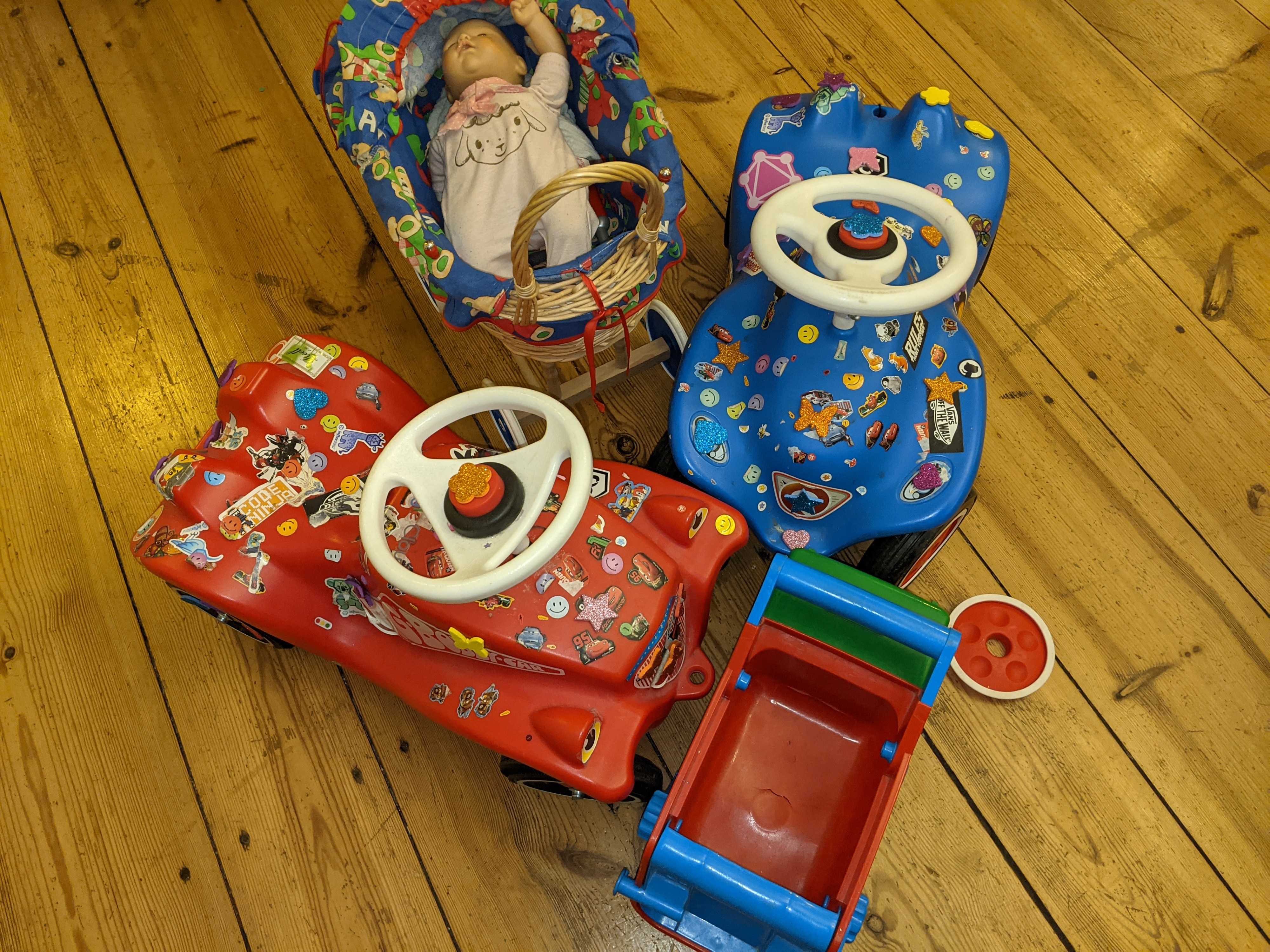 Toy cars and a toy baby carriage which have all run into each other.