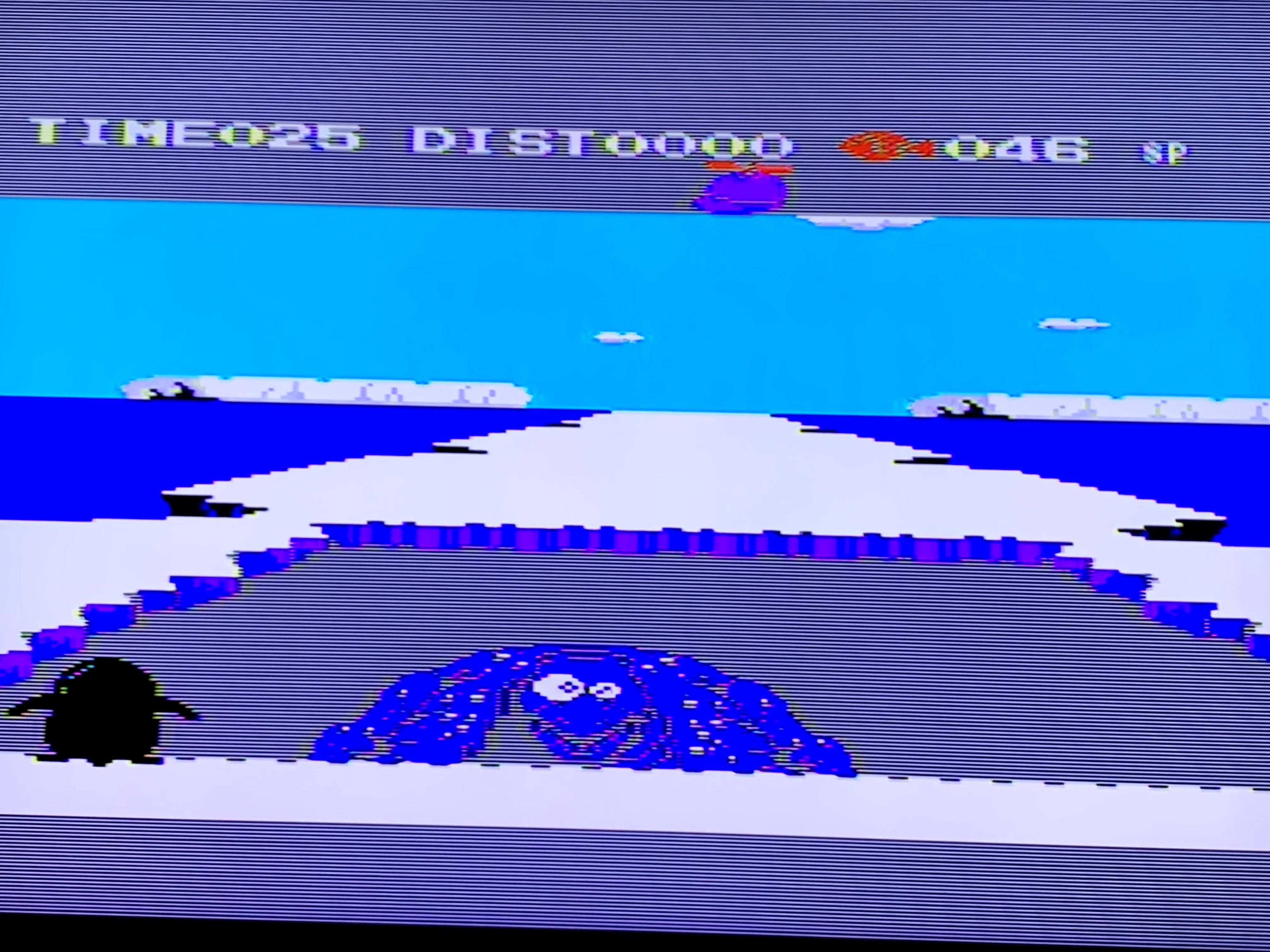 One of the boss rounds in Penguin Adventure. A Godzilla-like creature is about to fall into a hole in an arctic landscape.