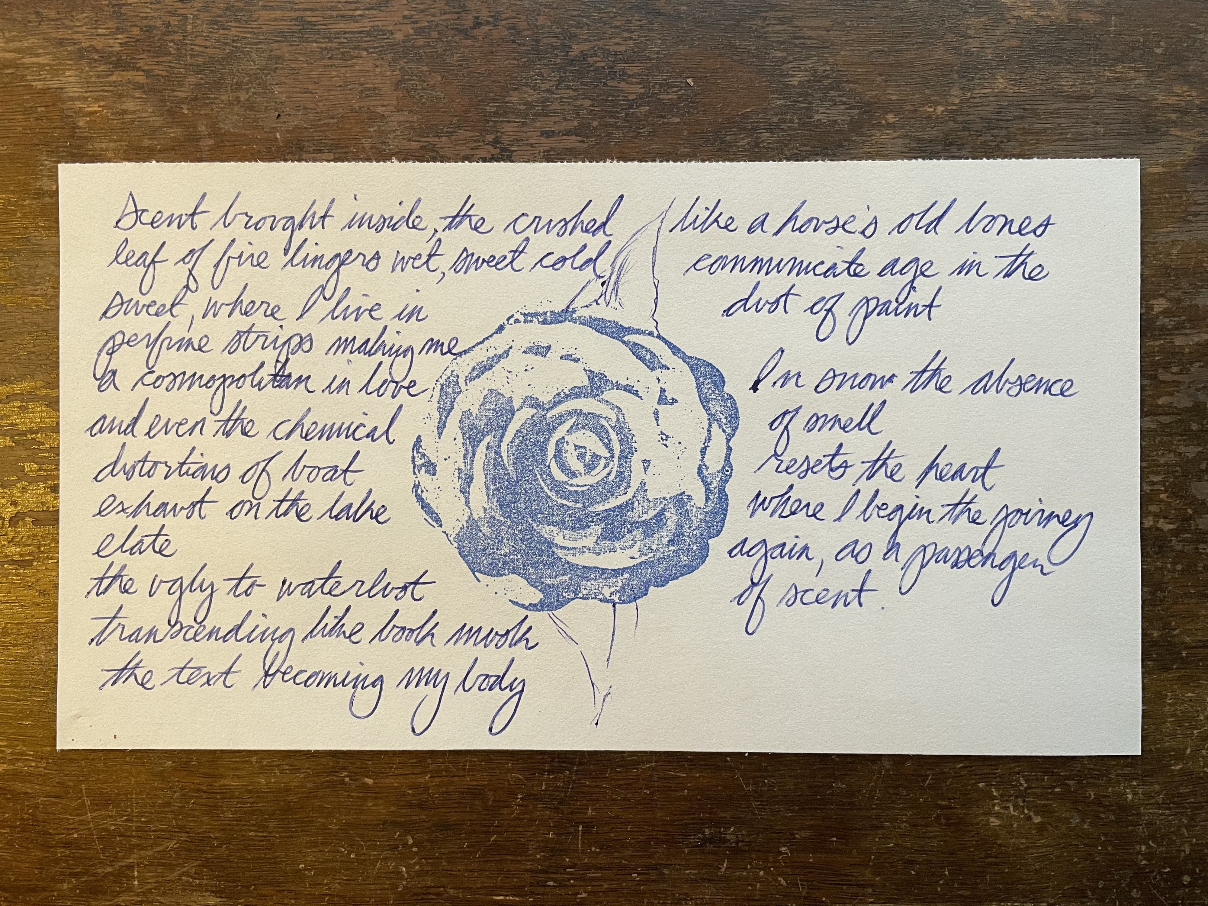 Photo of the poem with blie rose stamp on centre, paper reasting on weathered side table.