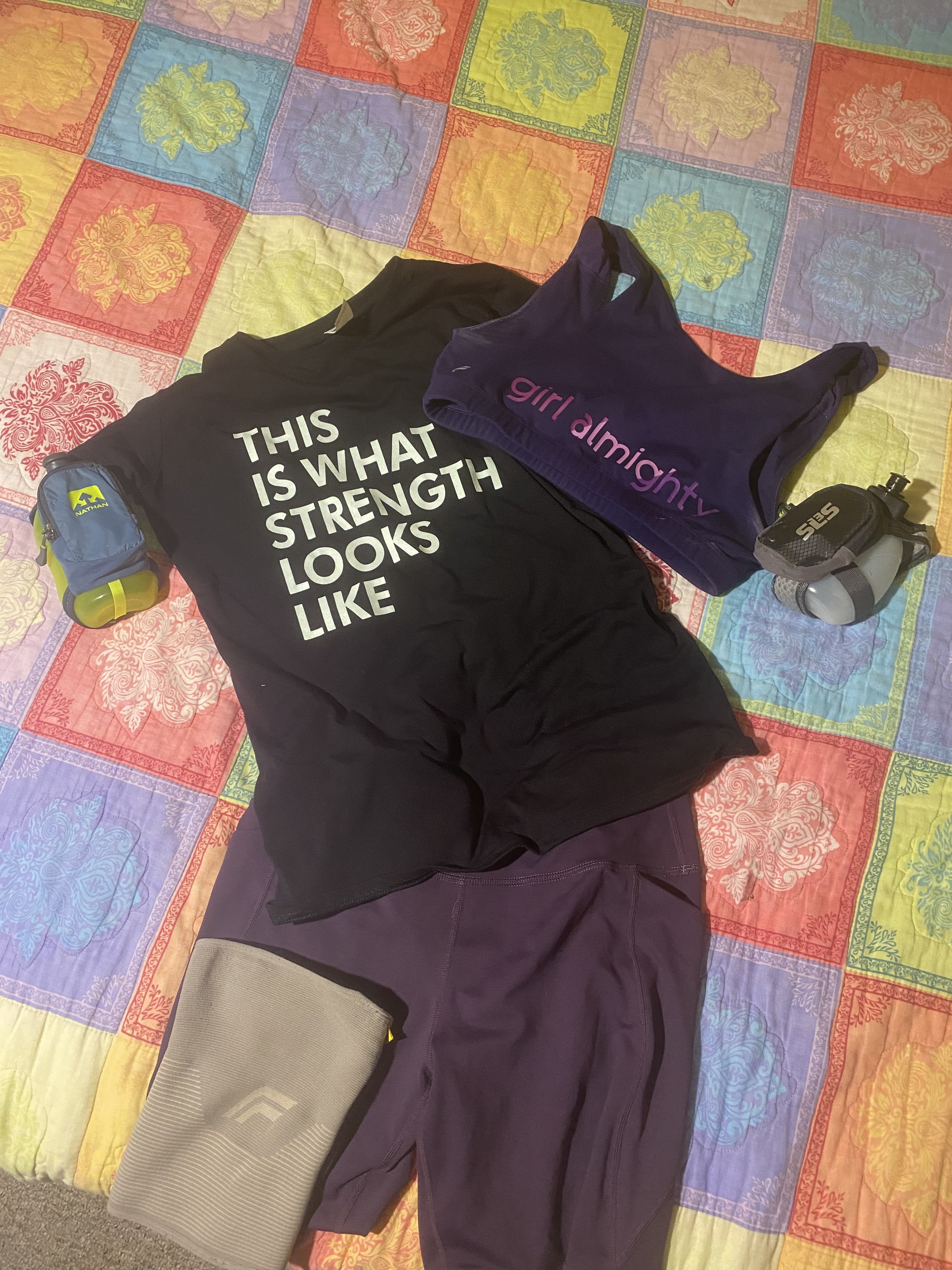 Amanda's race outfit: 2 handheld waterbottles, purple shorts, sports bra, & t-shirt reading THIS IS WHAT STRENGTH LOOKS LIKE
