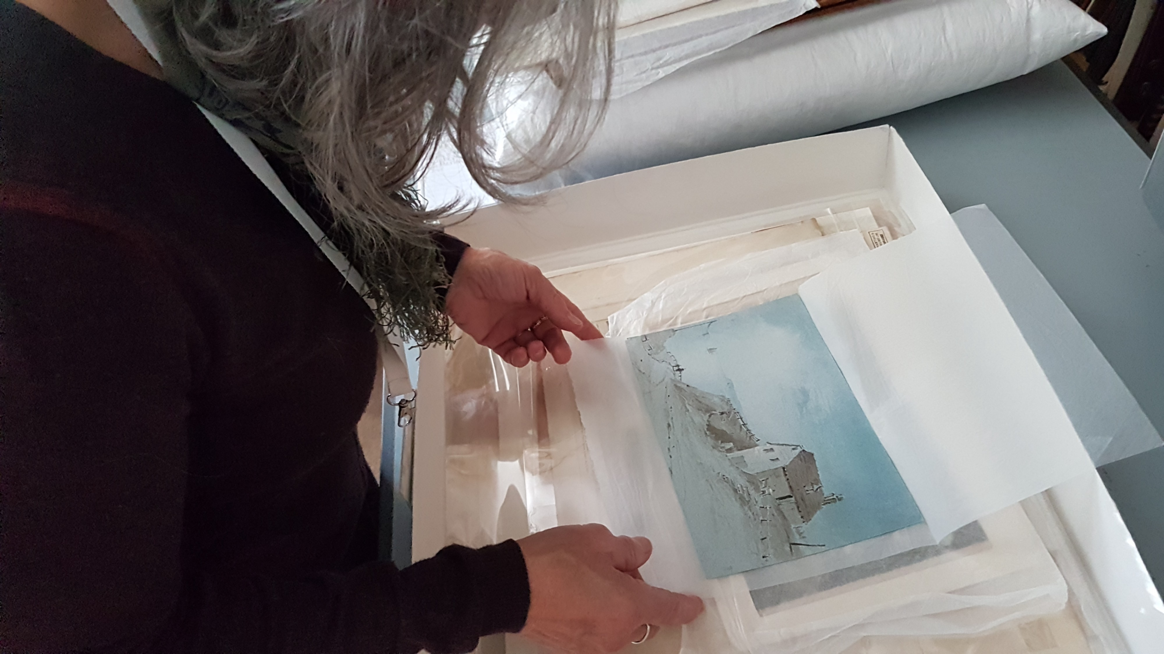 shows someone examining an engraving from a tissue paper-lined archive box. (Photo by Jon Pratty)