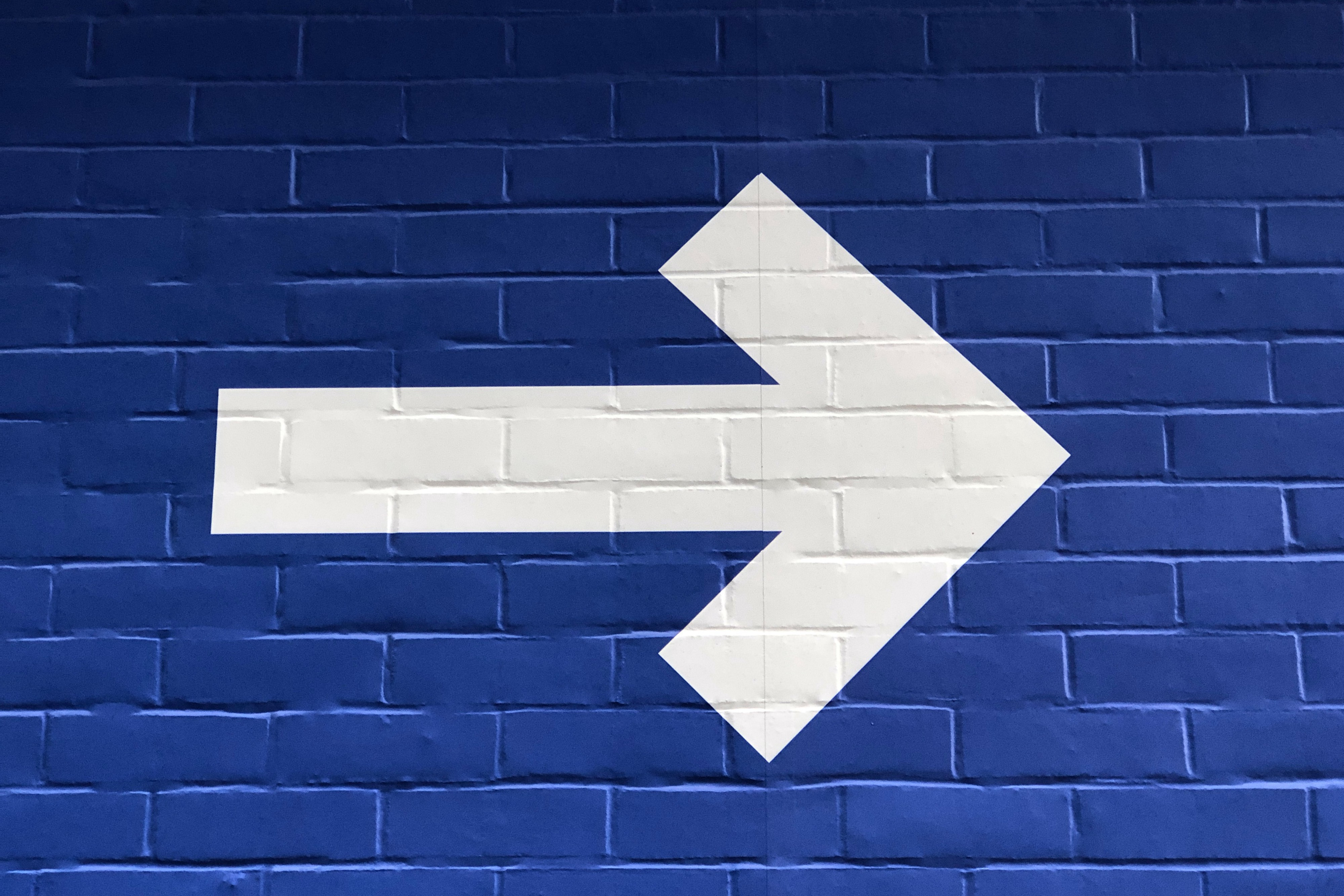 Painted white arrow on blue brick background.