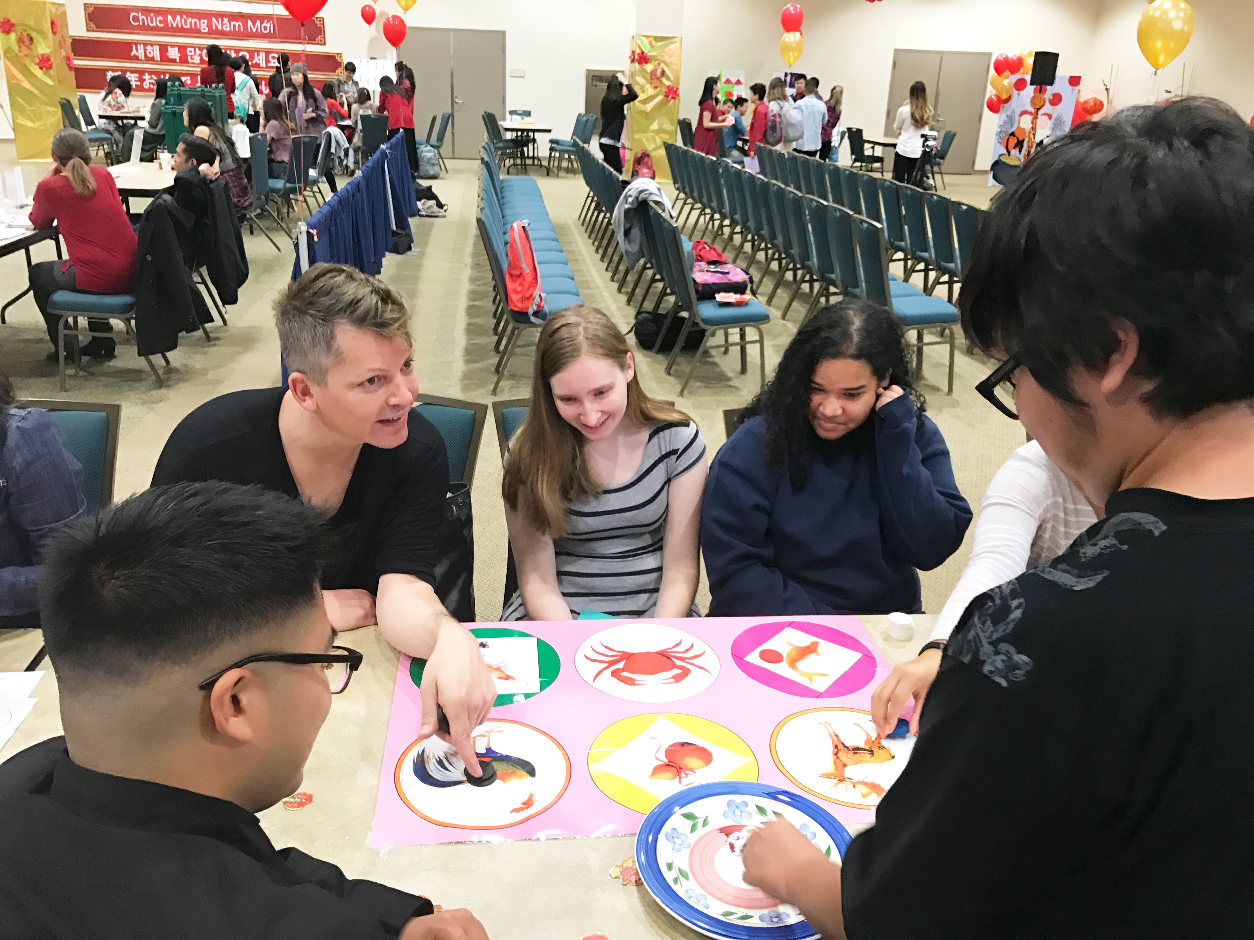 5 people are gathered around a table with circular illustrations playing a game. One man is pointing at a rooster drawing