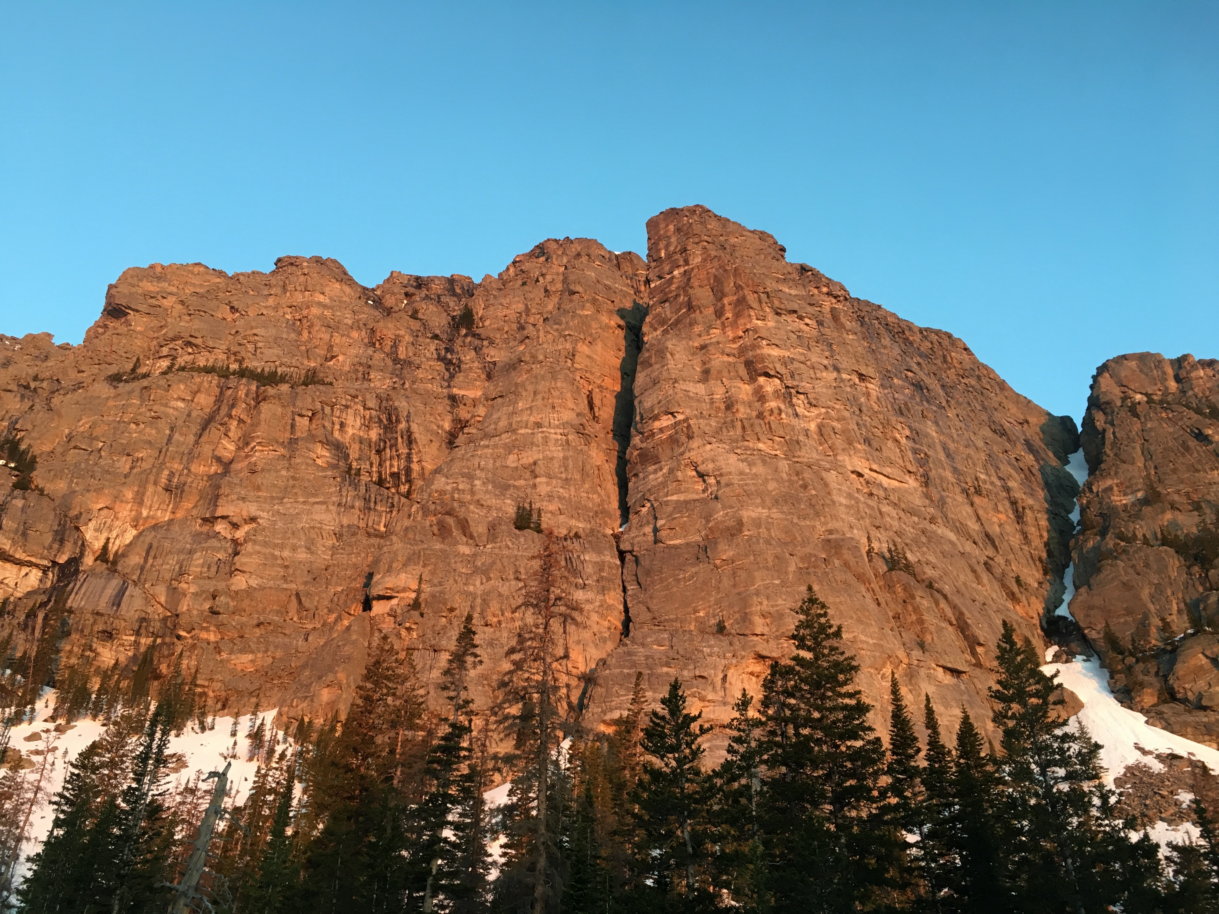 Alpenglow makes a rock wall glow pink against a luminous blue sky.