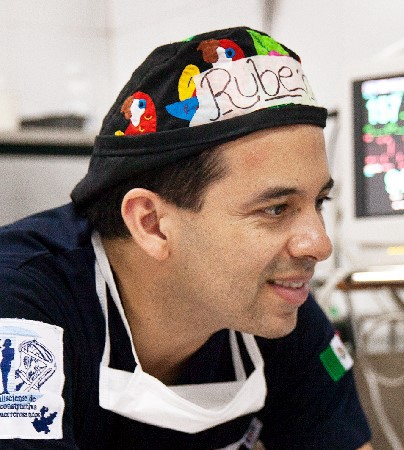 Dr. Ruben Ayala in scrubs caring for a patient.