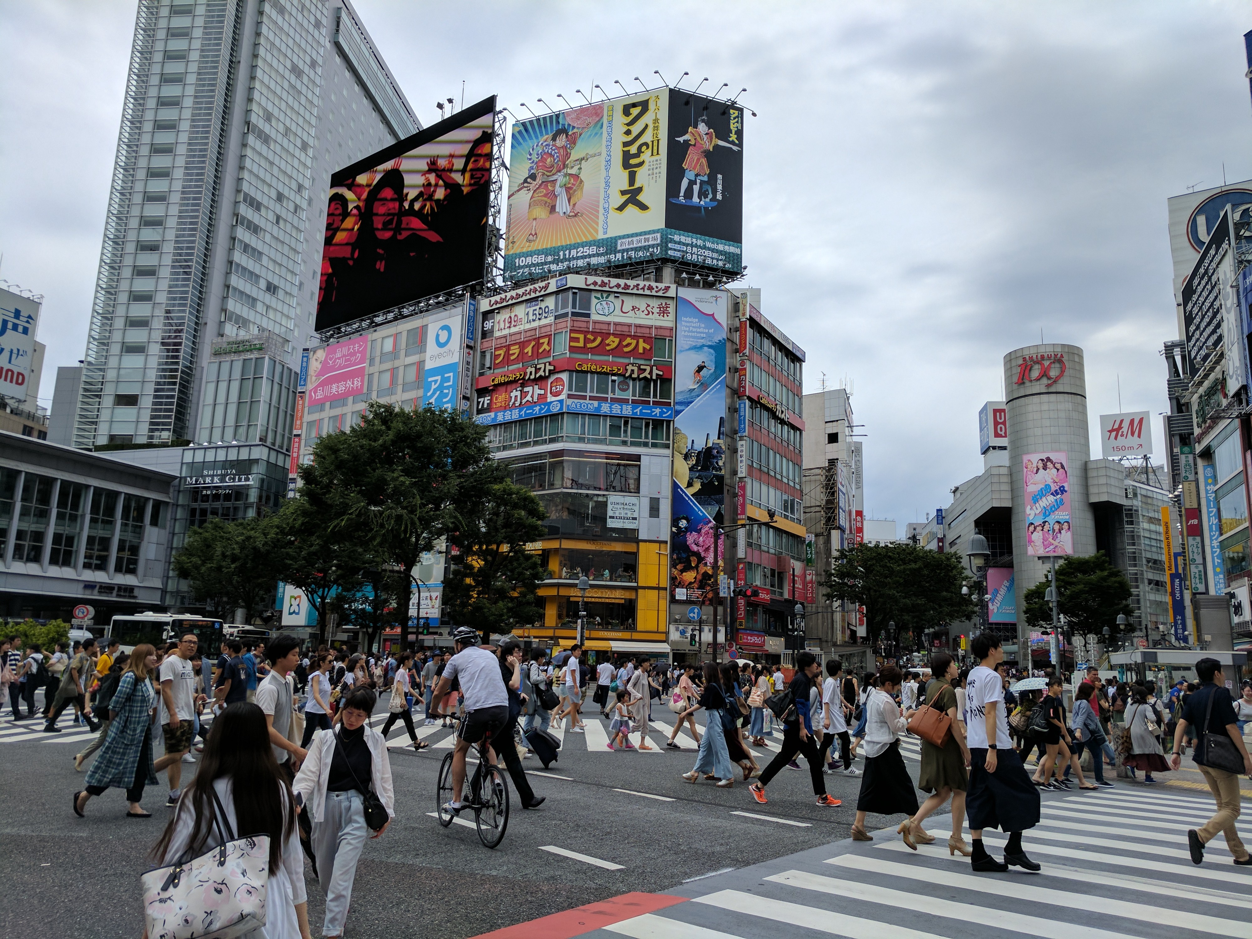 Shibuya Crossing in Tokyo. Masses of pedestrians and cyclists make their way across a very busy intersection. Tall buildings and billboards are in the background