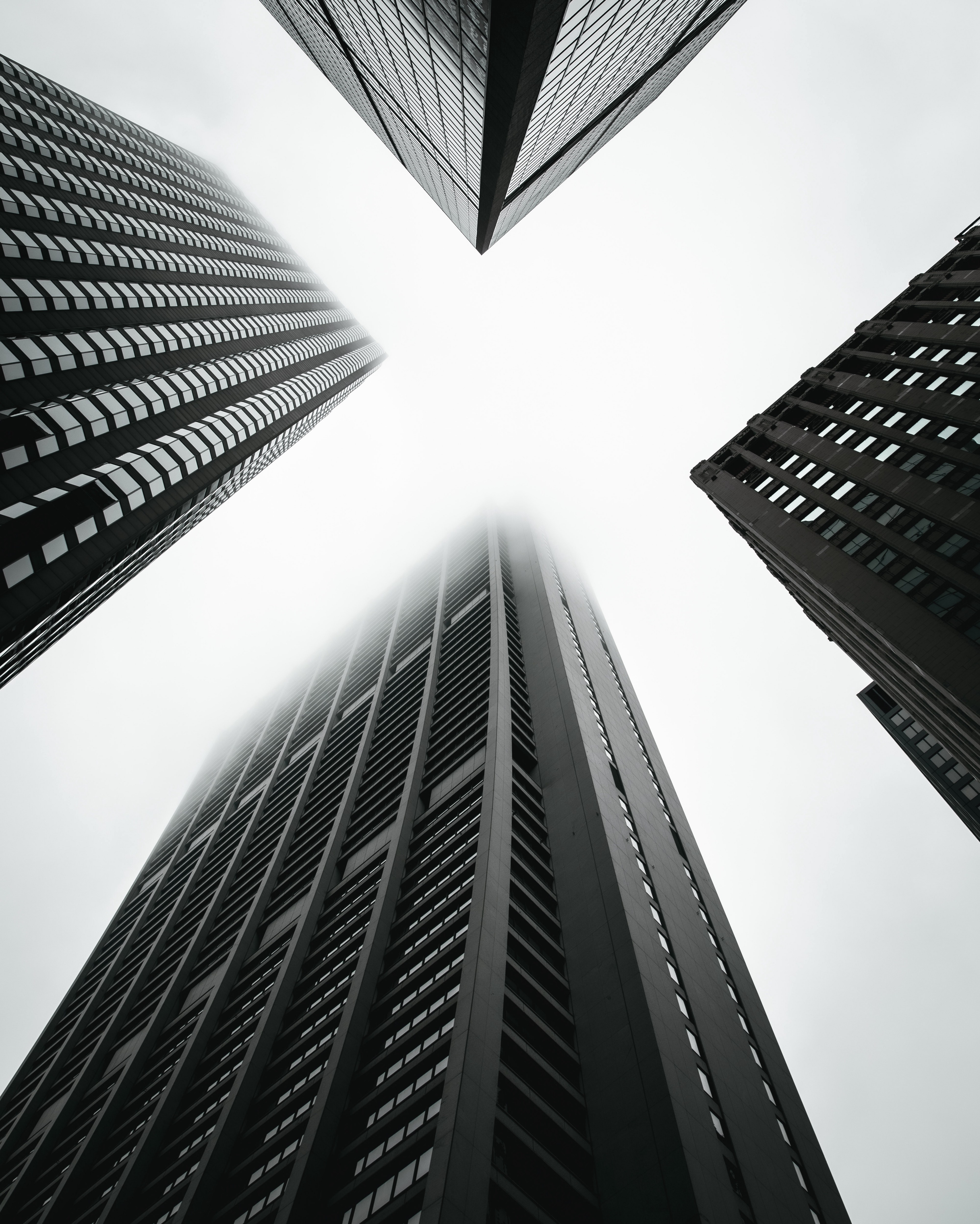 Tall buildings rise into the sky. Black-and-white photo.