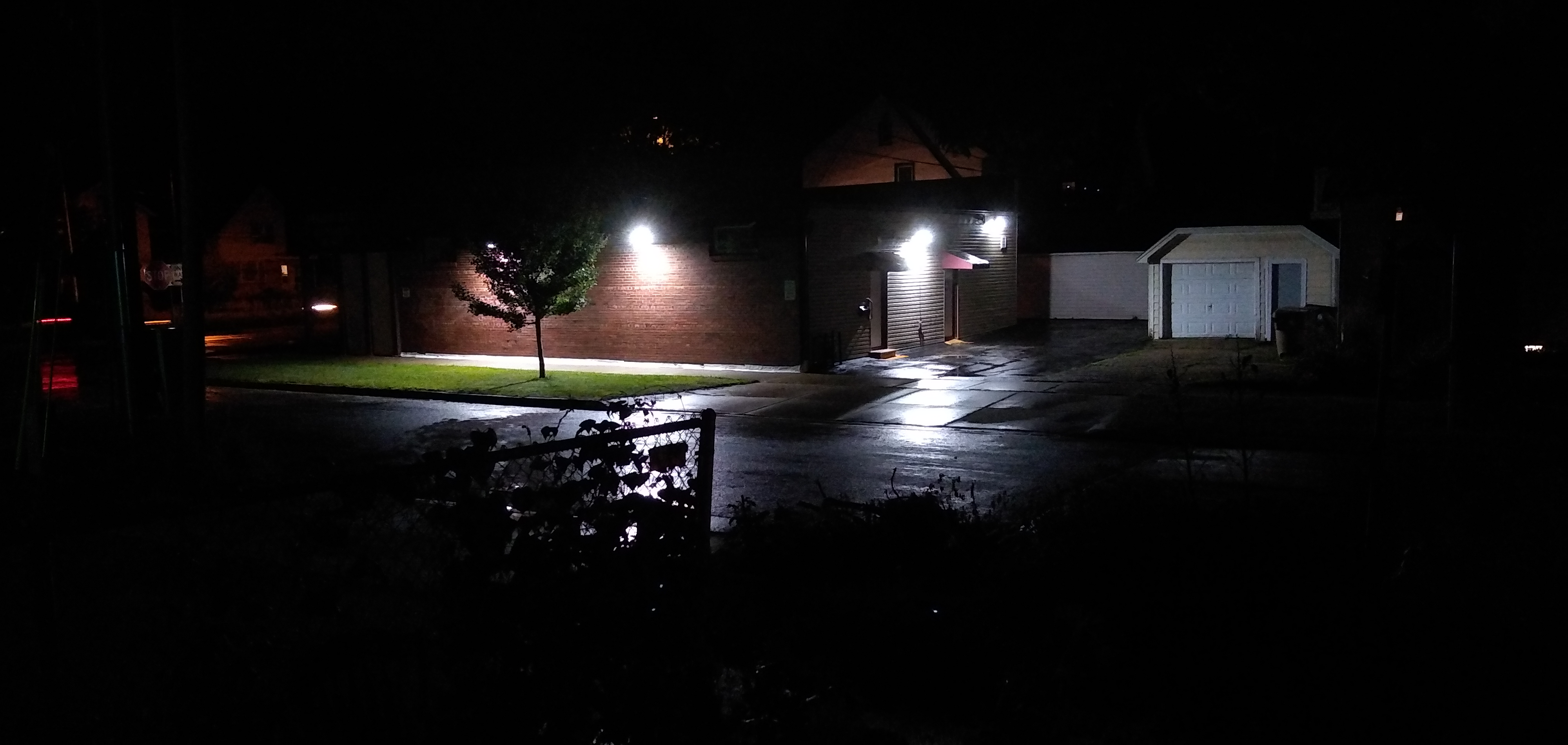 Lighted suburban street with a brick building and a fence at night