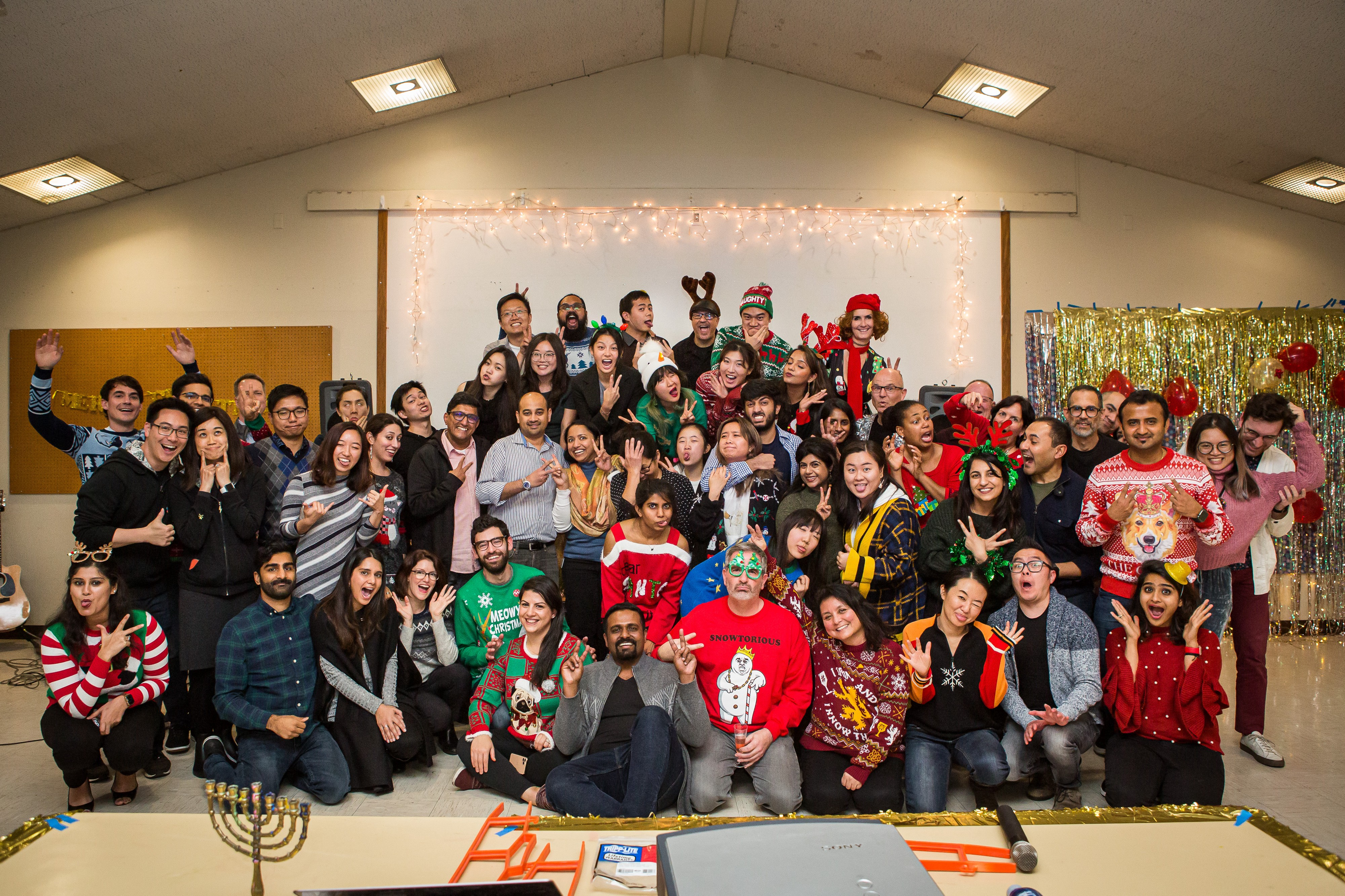 A design team making funny faces at their holiday party