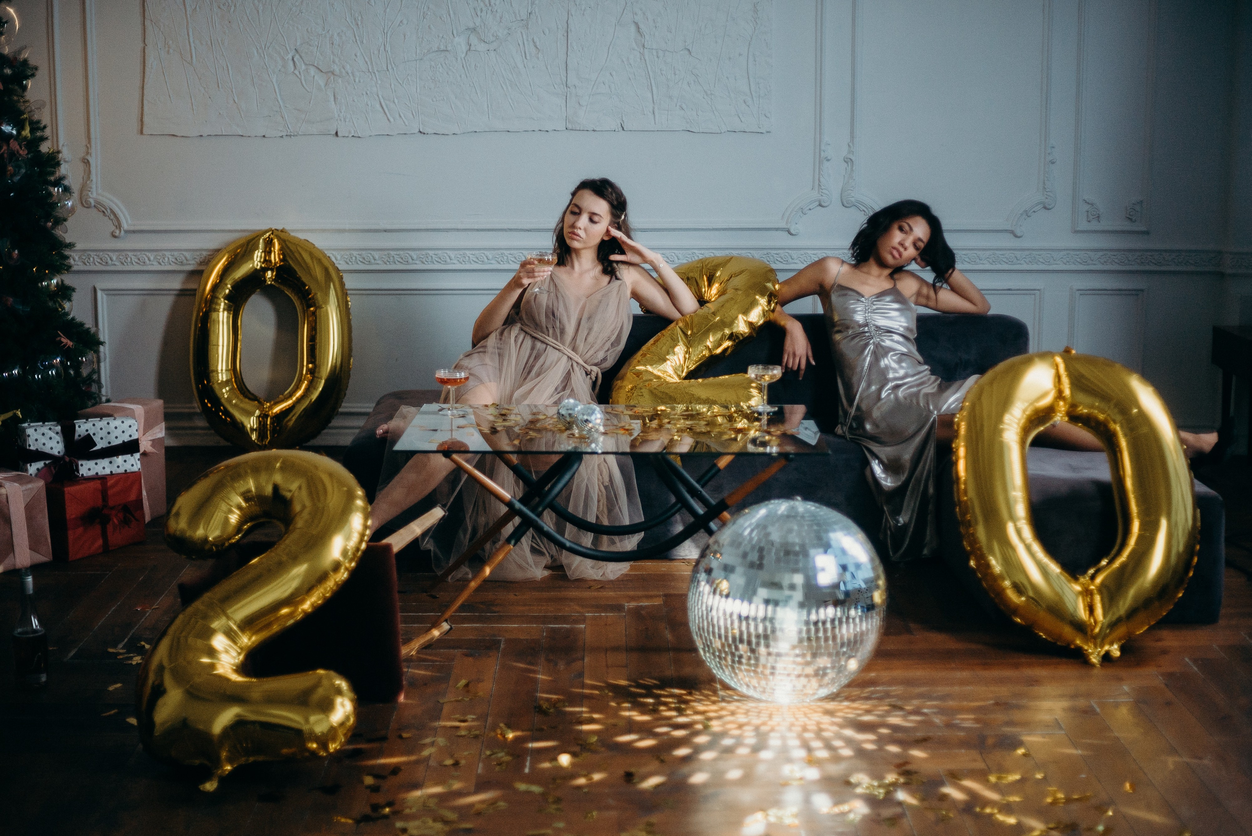 Two women sitting on sofa with 2020 baloons