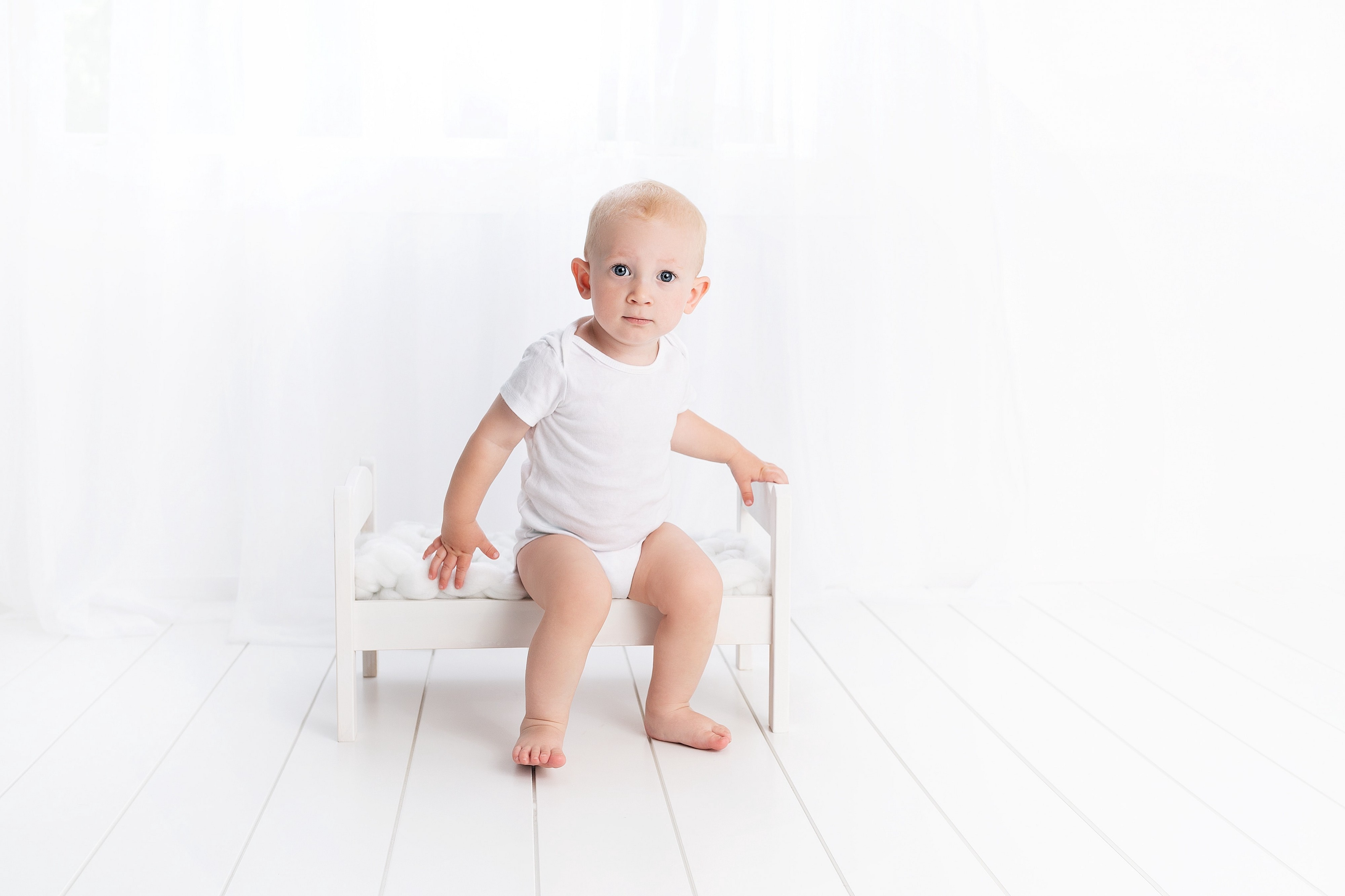 Toddler wearing a white tshirt and white underpants, sitting on a white chair in a white room