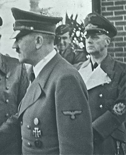 Von Ribbentrop standing behind Hitler. Von Ribbentrop is in uniform and looks much older than Hitler.