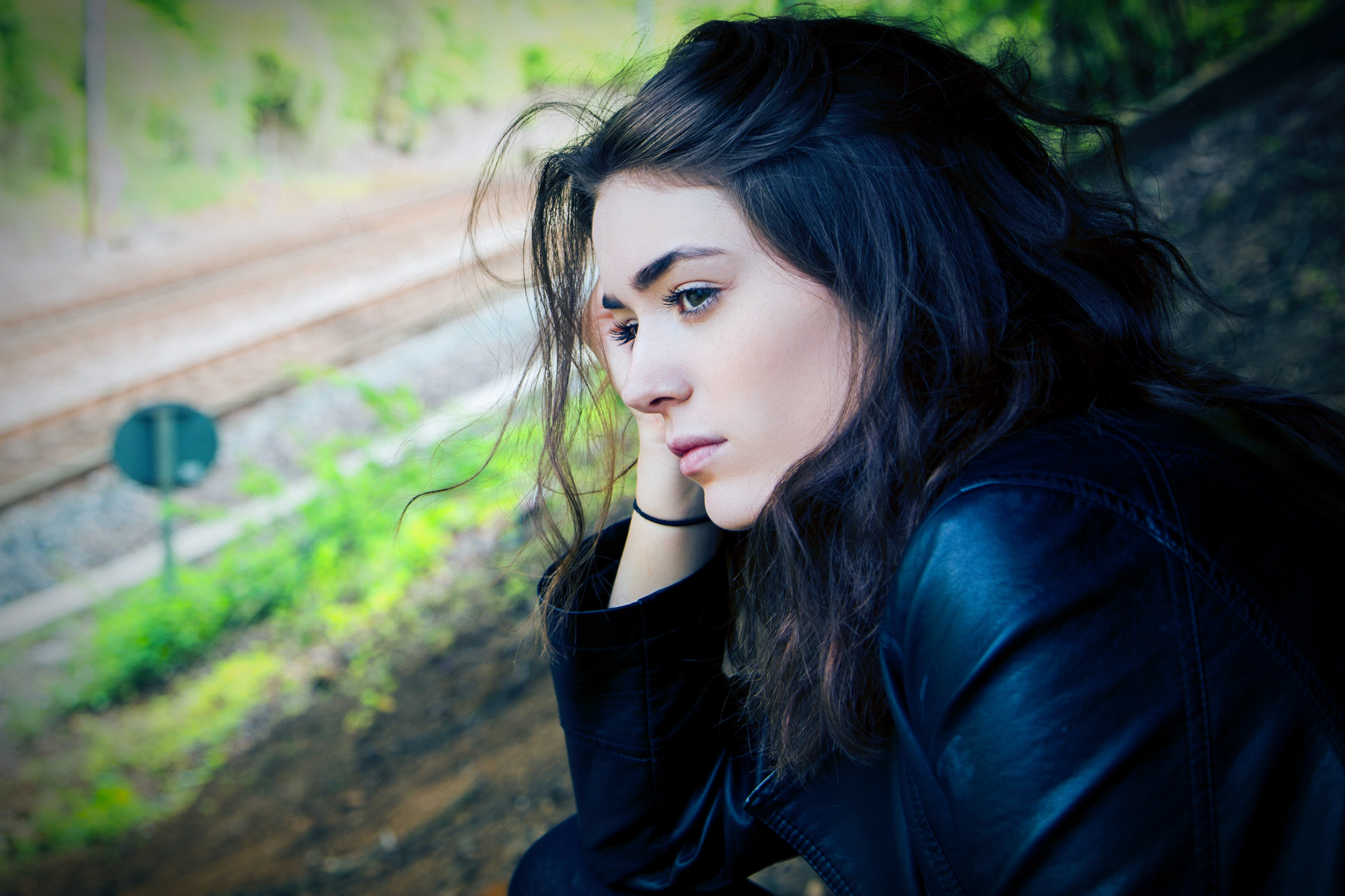 girl with long dark hair wearing black leather jacket looking thoughtful