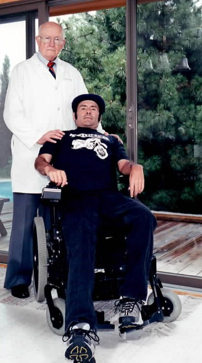 Craig Vetovitz in his wheelchair, with Dr. White standing behind