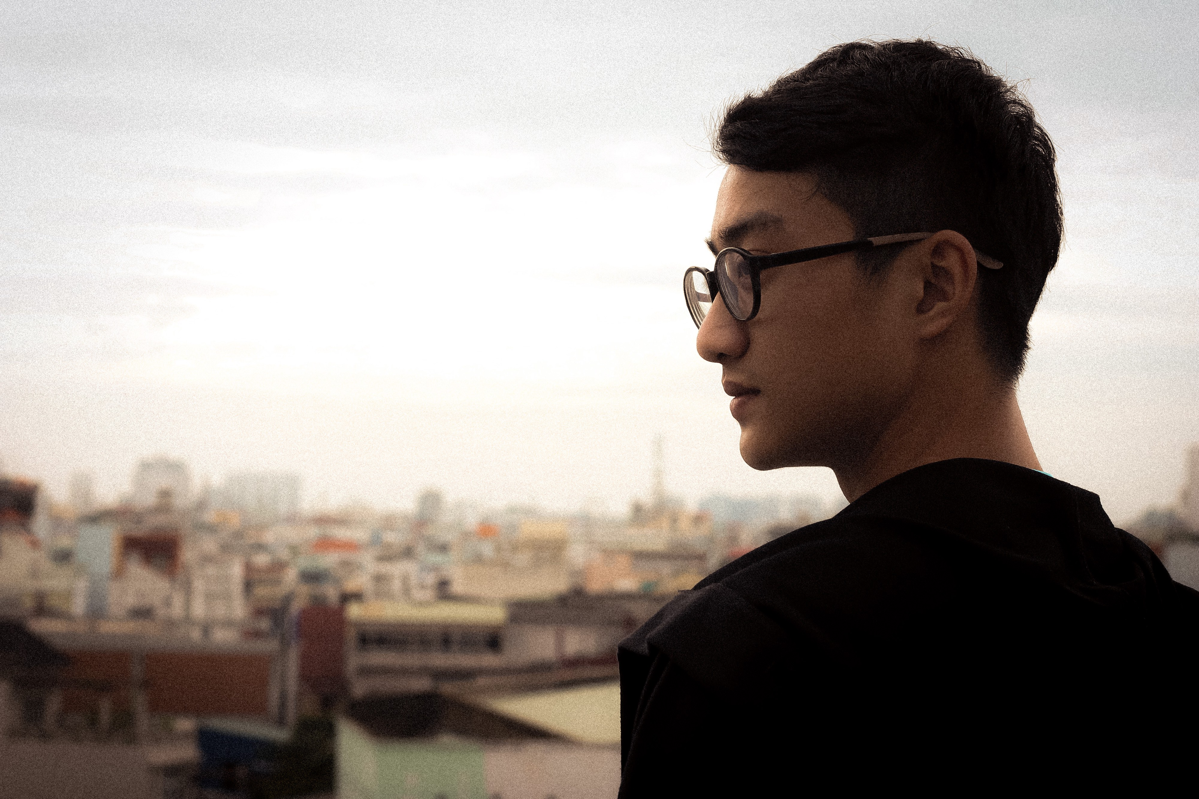 Man with glasses standing on rooftop looking sideways.