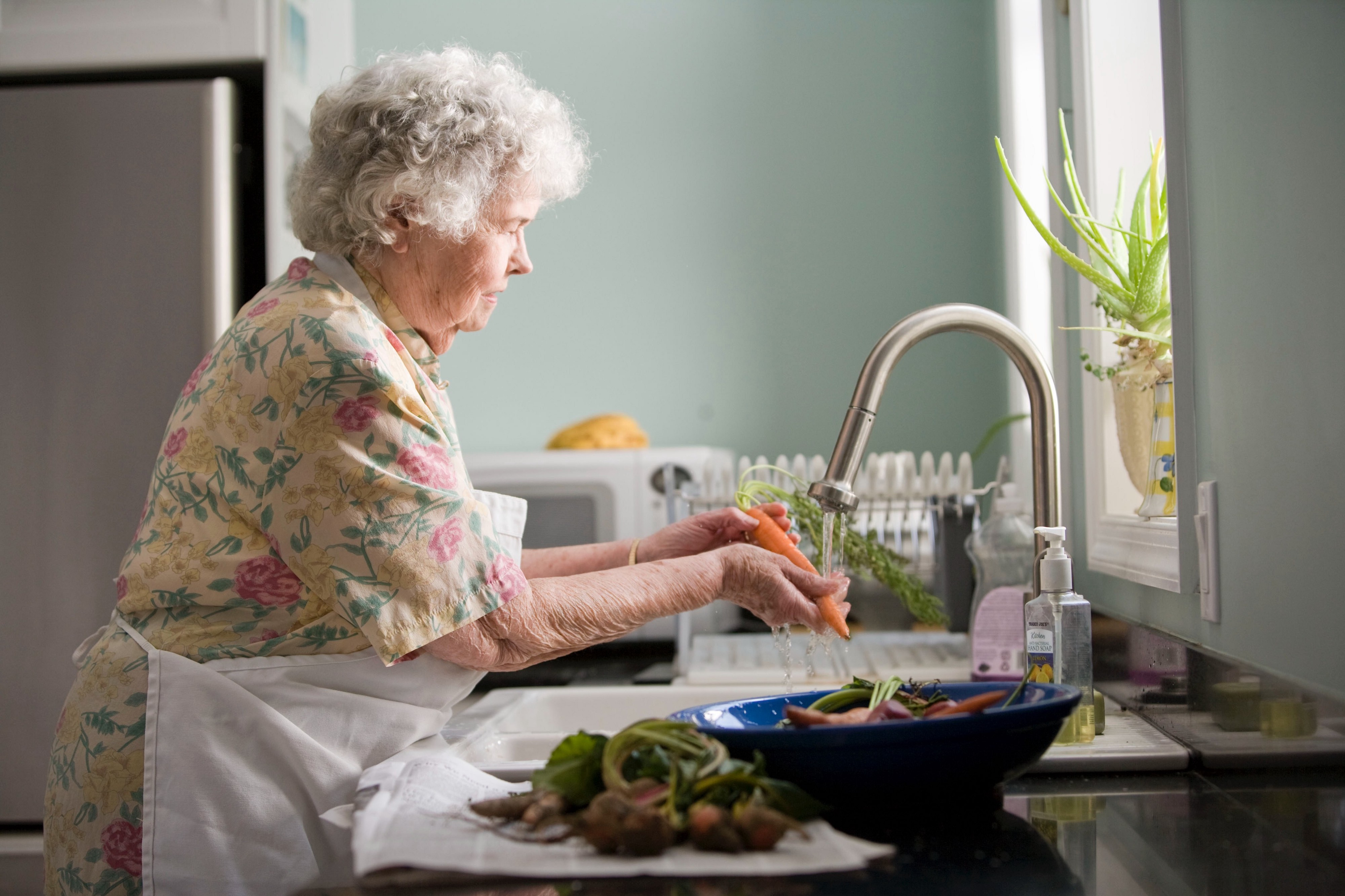 Grandmotherly woman washing vegetables at the kitchen sink.