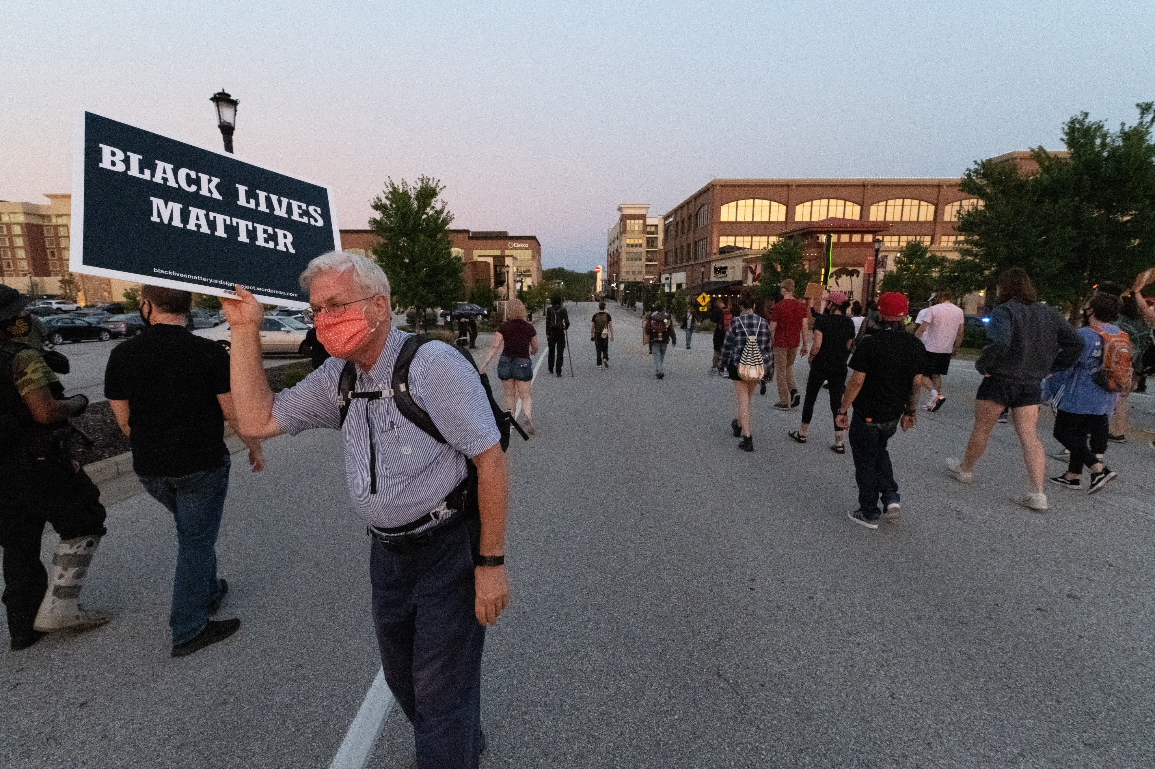 A man holds a Black Lives Matter sign as protesters march in St. Charles, MO.