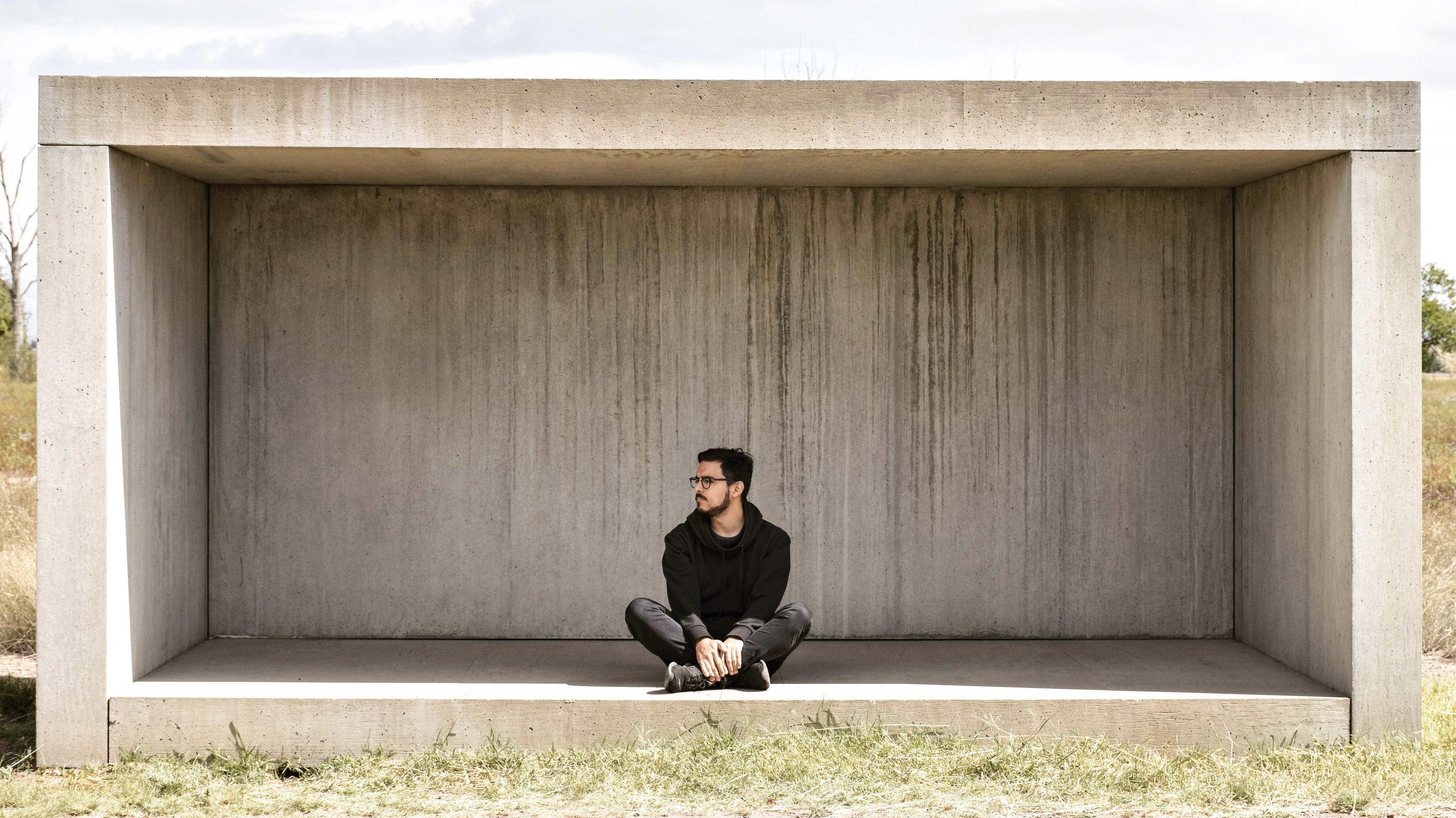 man with dark hair wearing glasses sitting cross-legged on concrete structure
