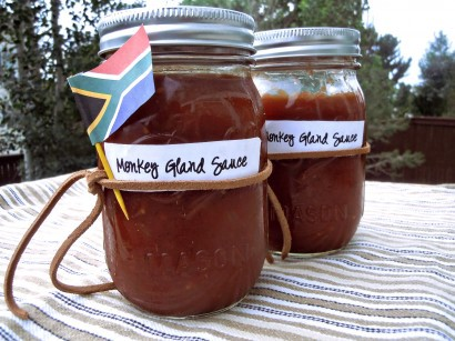Two canning jars full of red sauce with a little paper South African flag on one of them