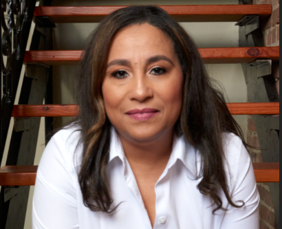 Simone Spence sitting in front of a set of stairs and brick wall
