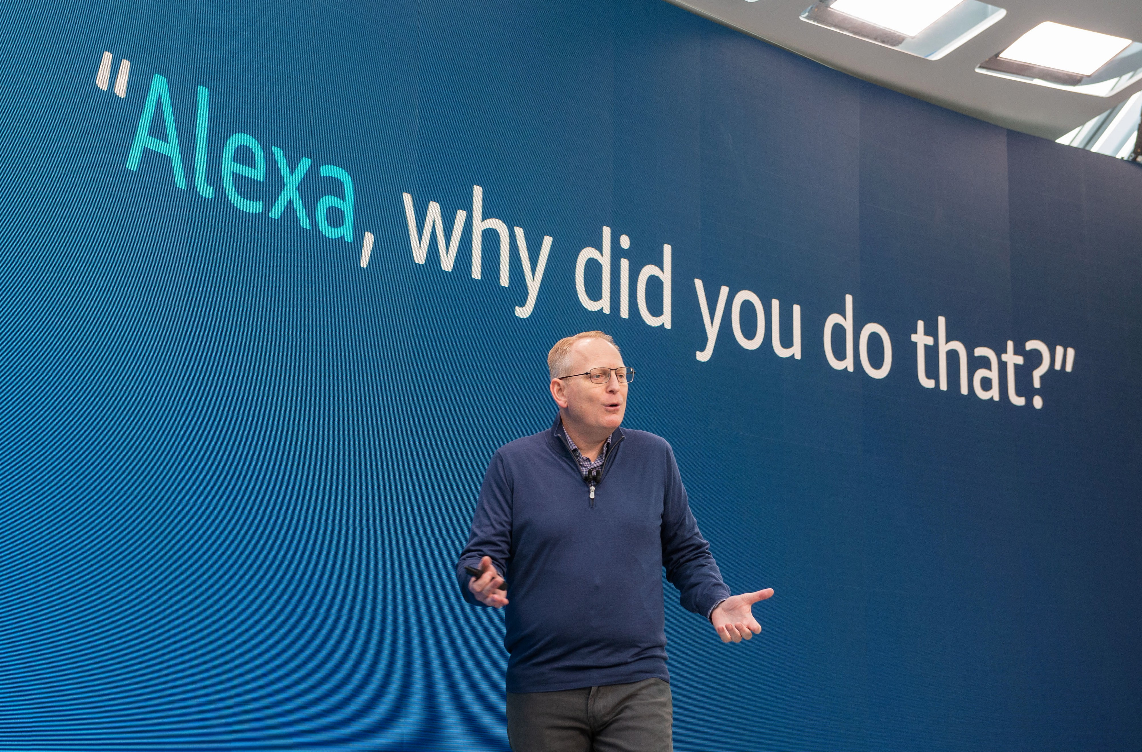 """Amazon senior VP Dave Limp demonstrates a new Alexa feature. The text """"Alexa, why did you do that?"""" is showcased behind him."""