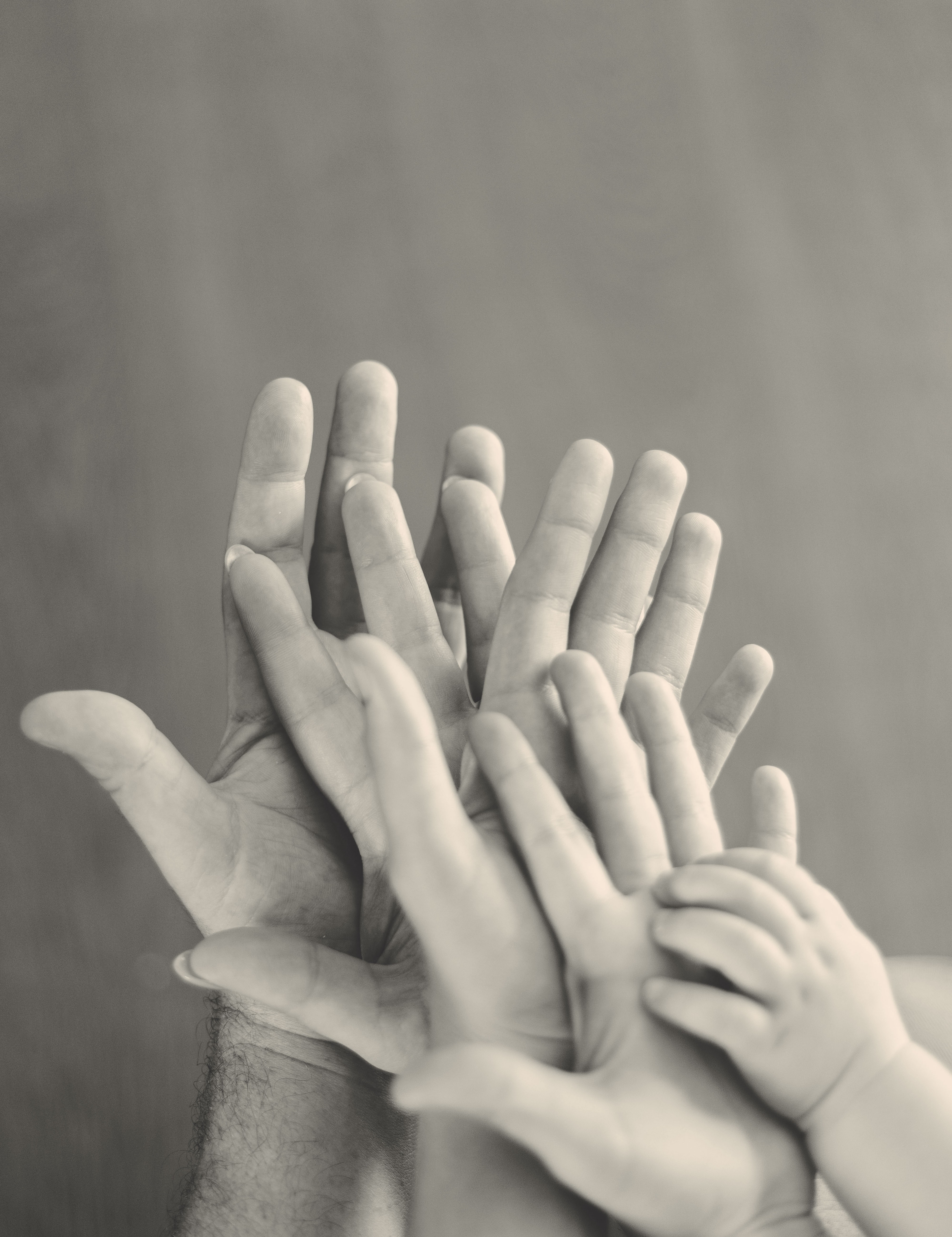 A black and white shot of five hands in varying sizes, depicting caregivers and their child.